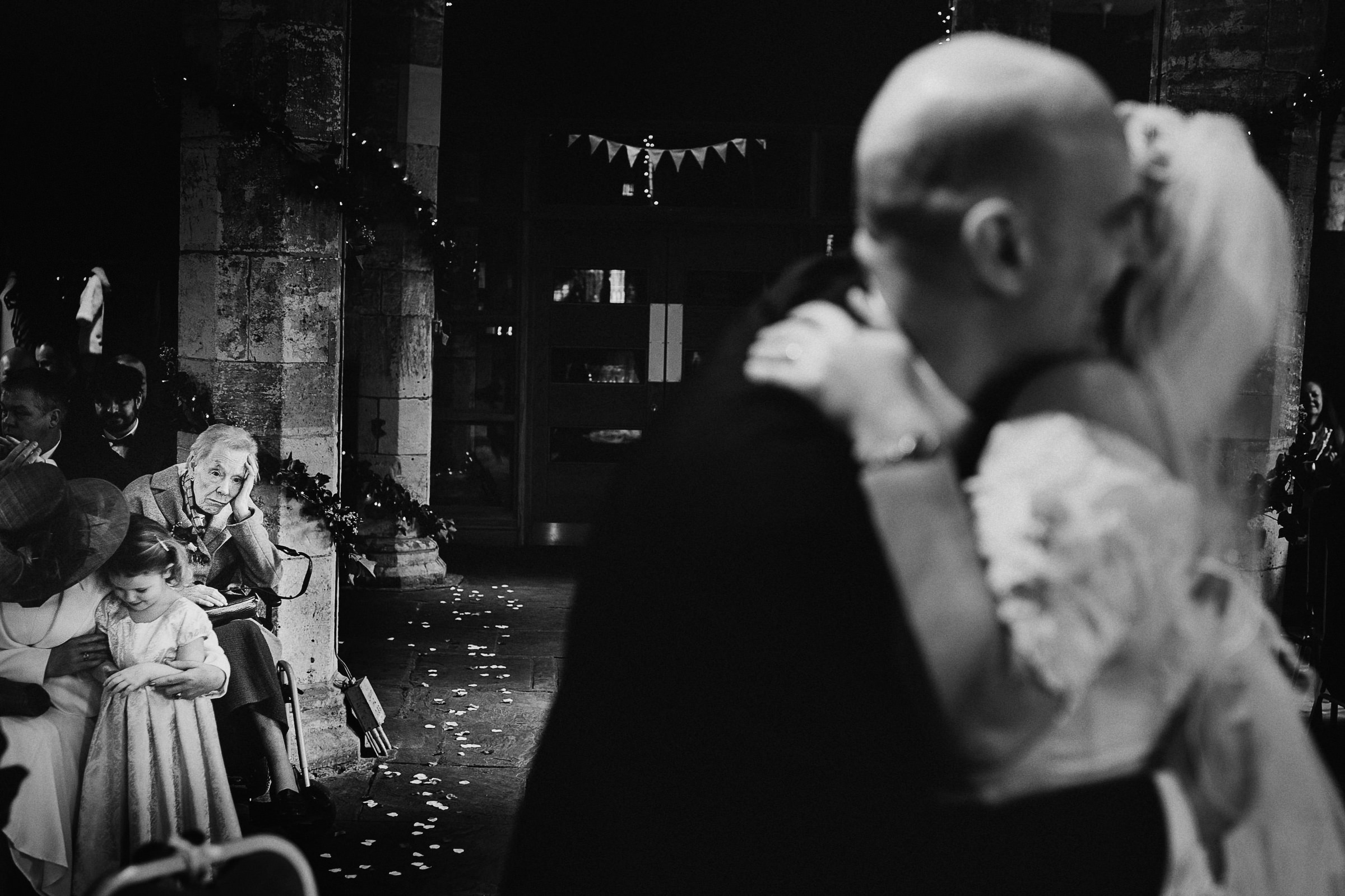 Tired grandmother with little girl while couple dances - photo by Andy Gaines Photography