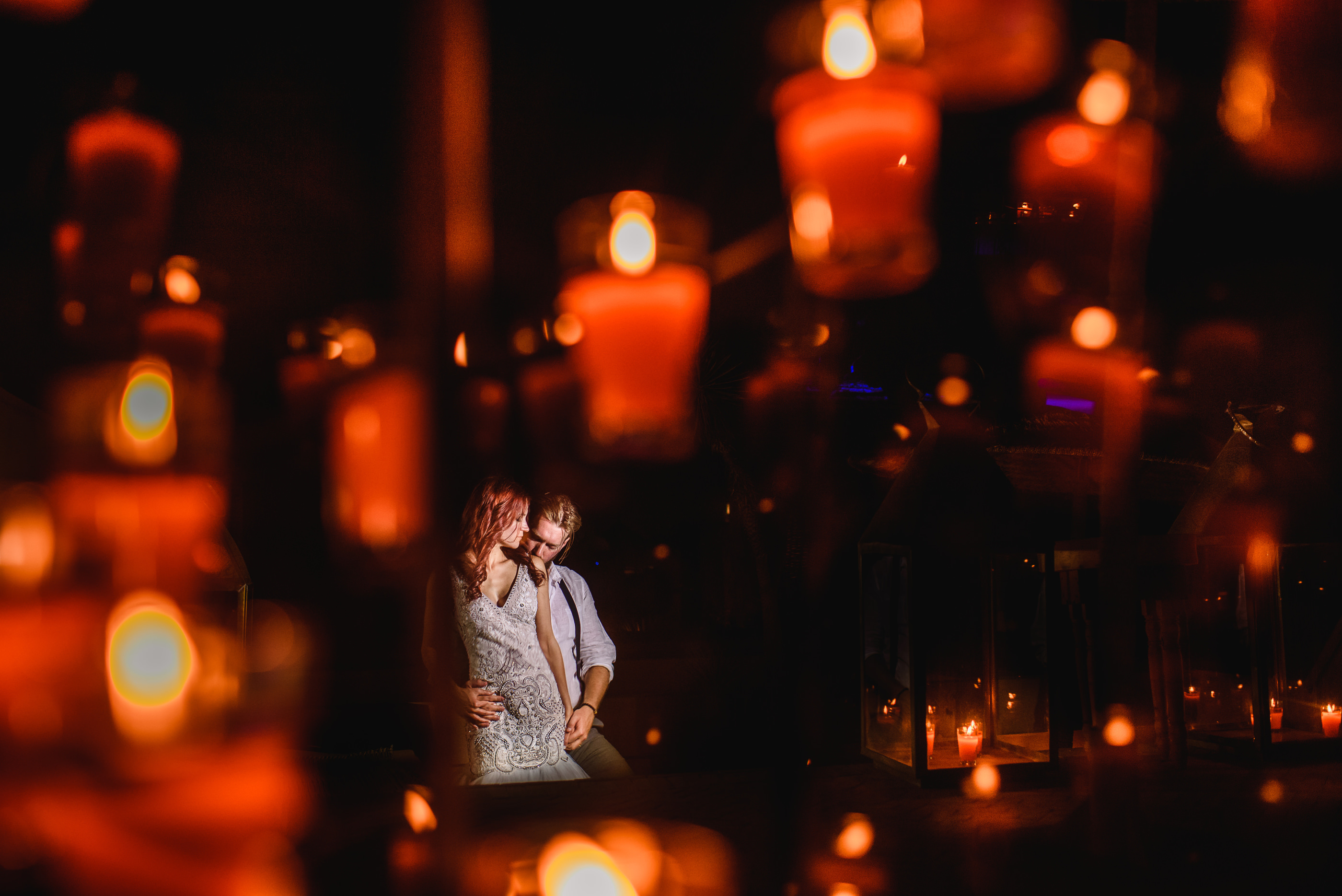 Couple dwarfed by red candles - photo by Andy Gaines Photography