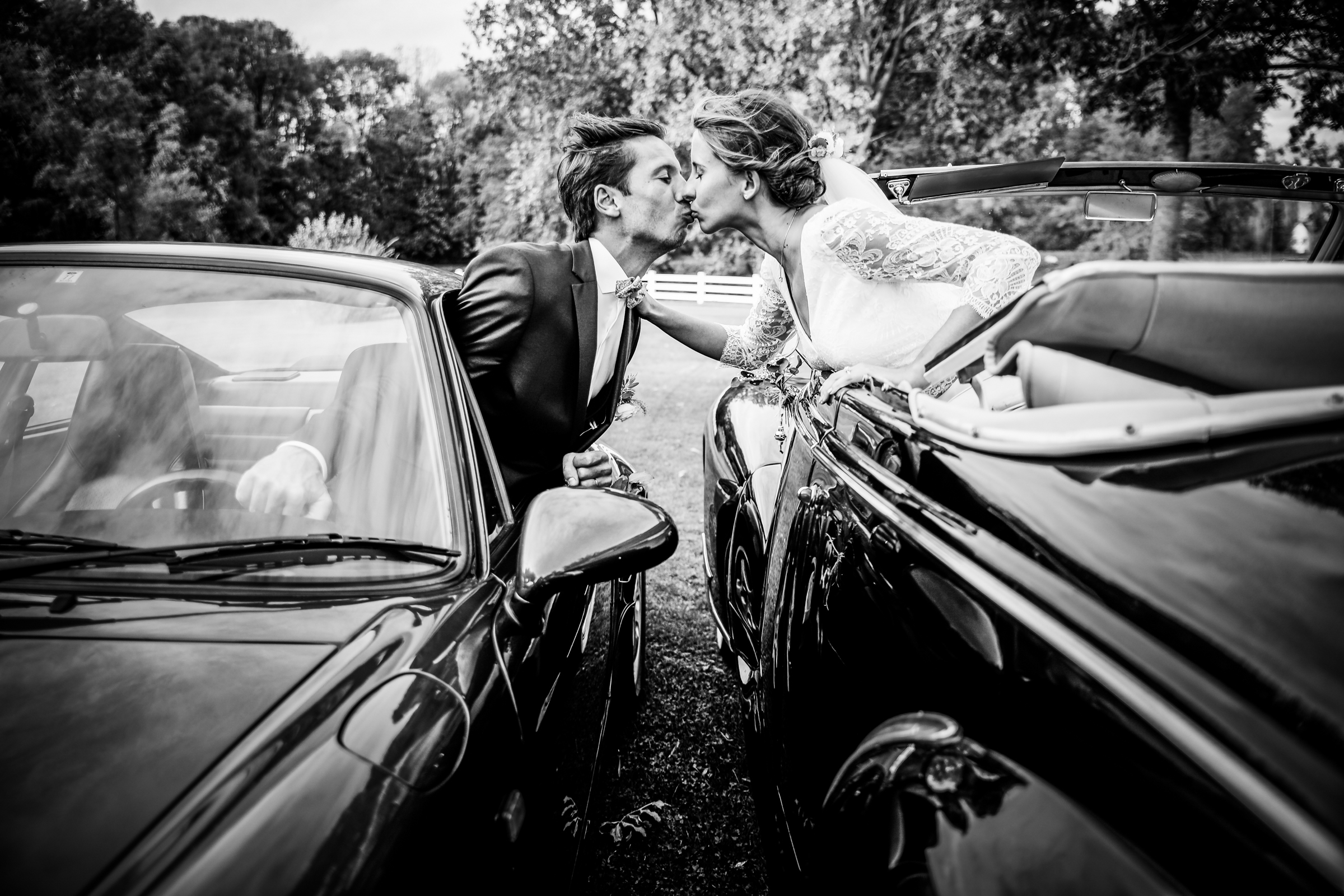 Bride and groom kiss across cars - photo by Julien Laurent-Georges