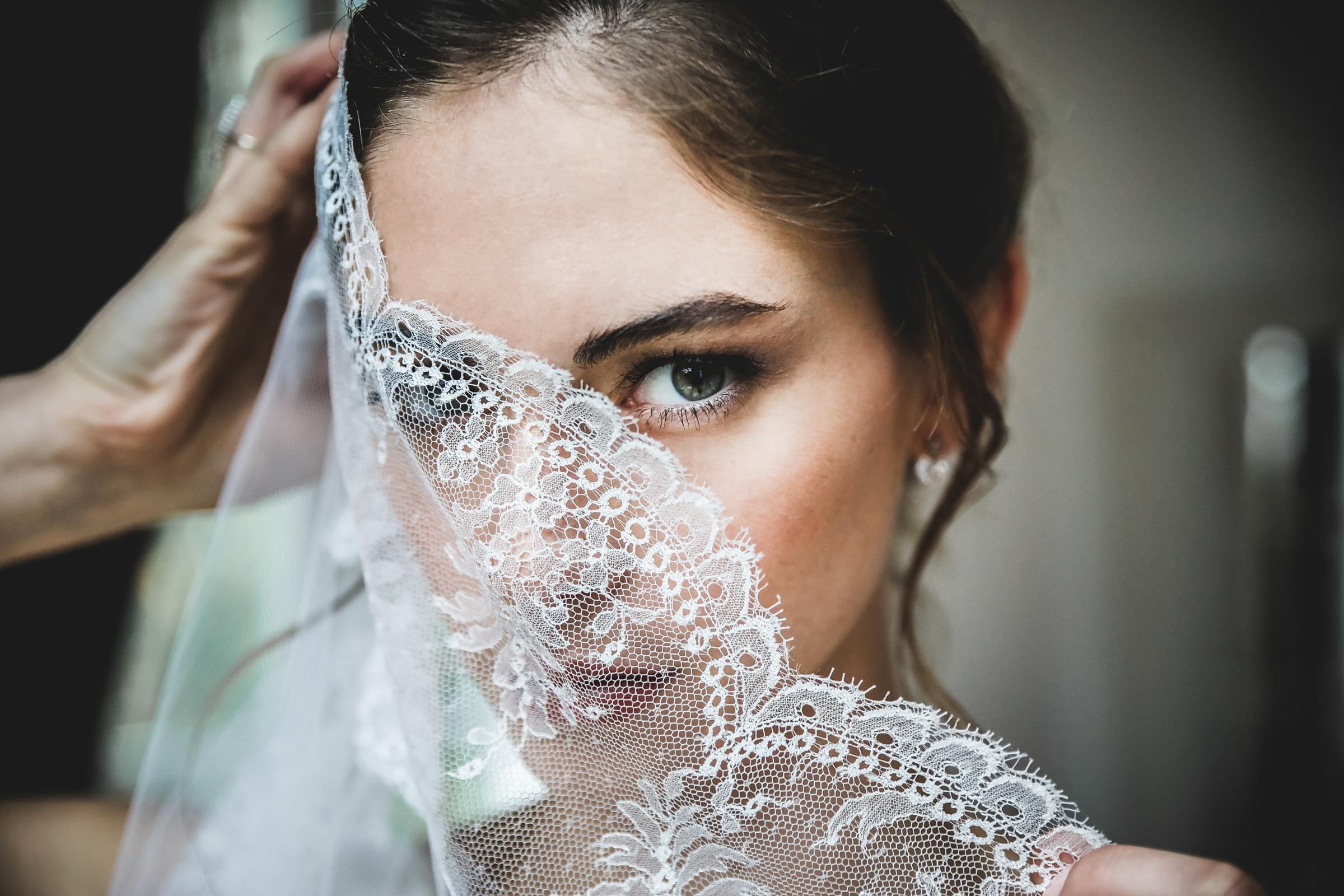 Bride peering through lace - photo by Julien Laurent-Georges