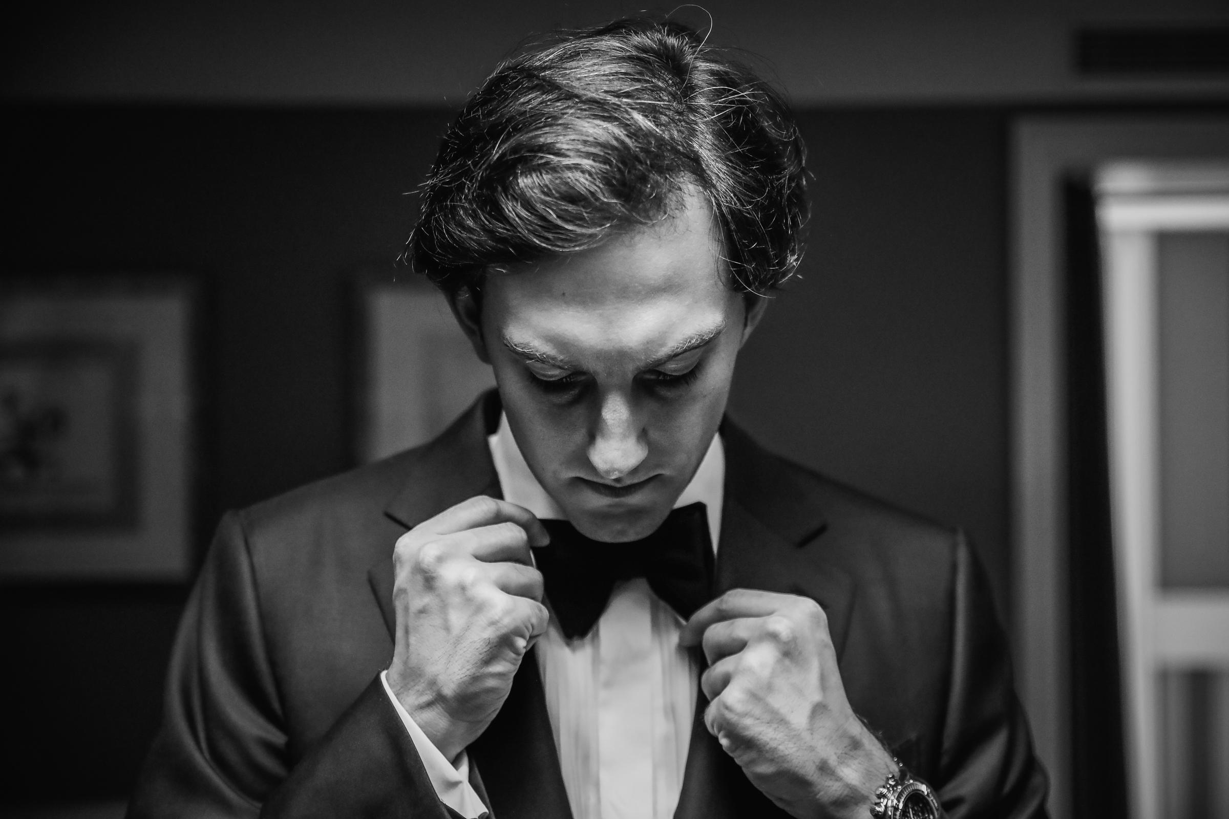 Groom adjusting bowtie - photo by Julien Laurent-Georges