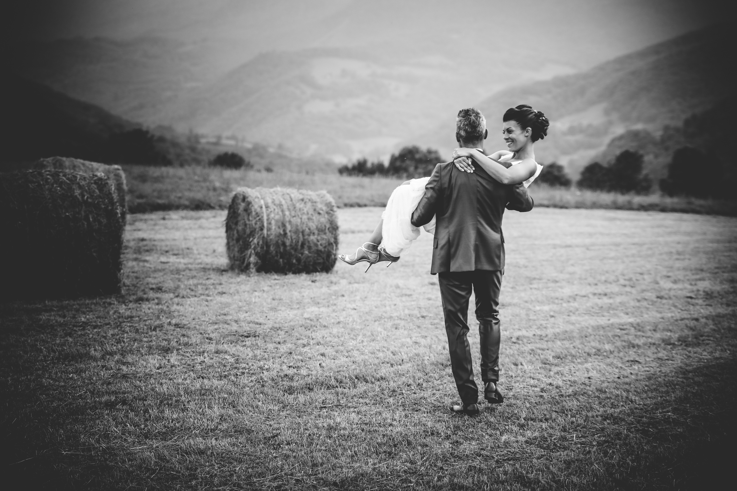 Groom carries bride over threshold to hay field - photo by Julien Laurent-Georges