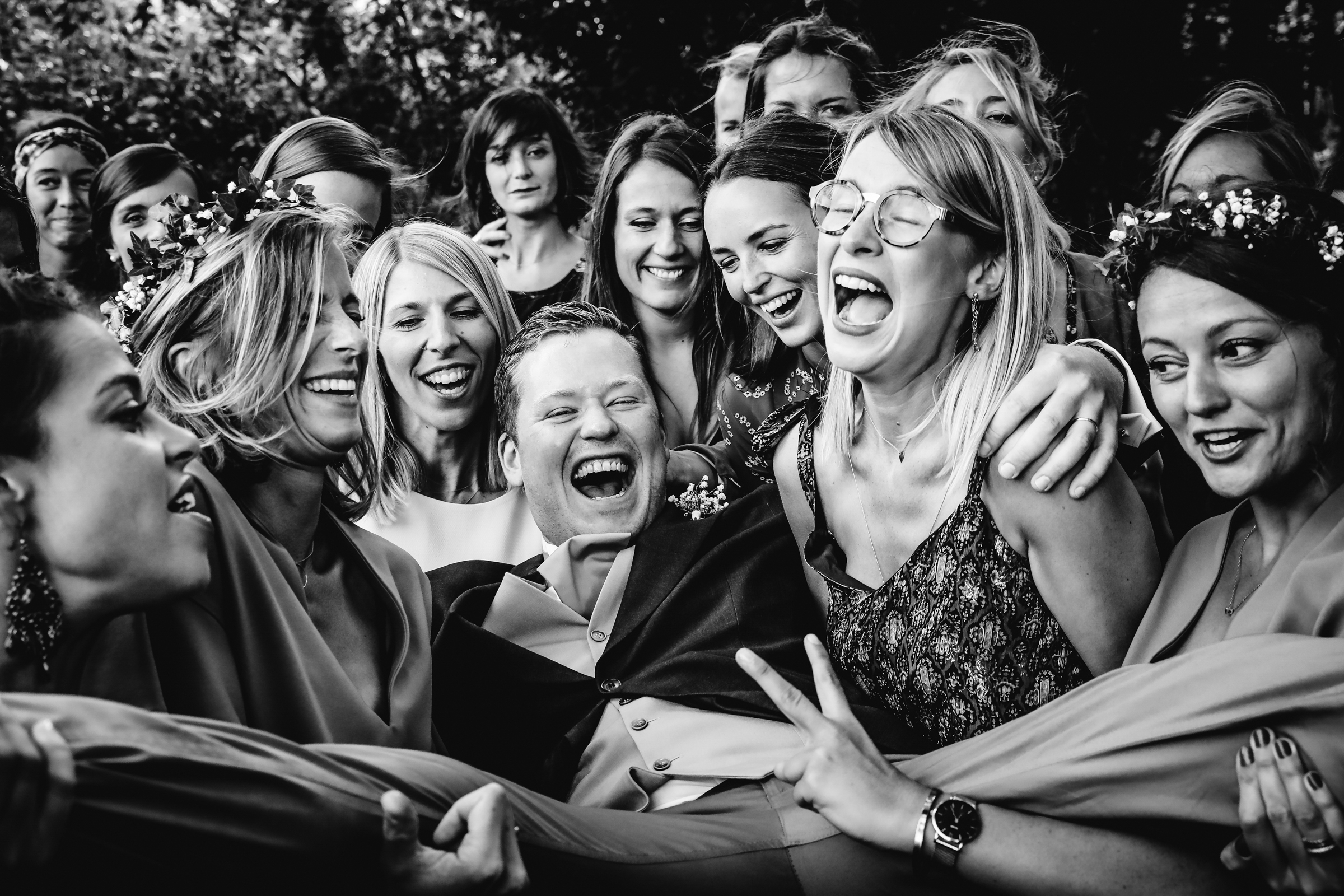Laughing guests carrying the groom- photo by Julien Laurent-Georges