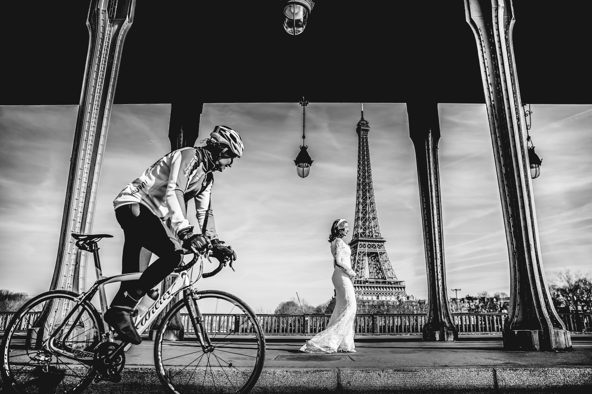 Man on bike passes bride near Eiffel Tower - photo by Julien Laurent-Georges