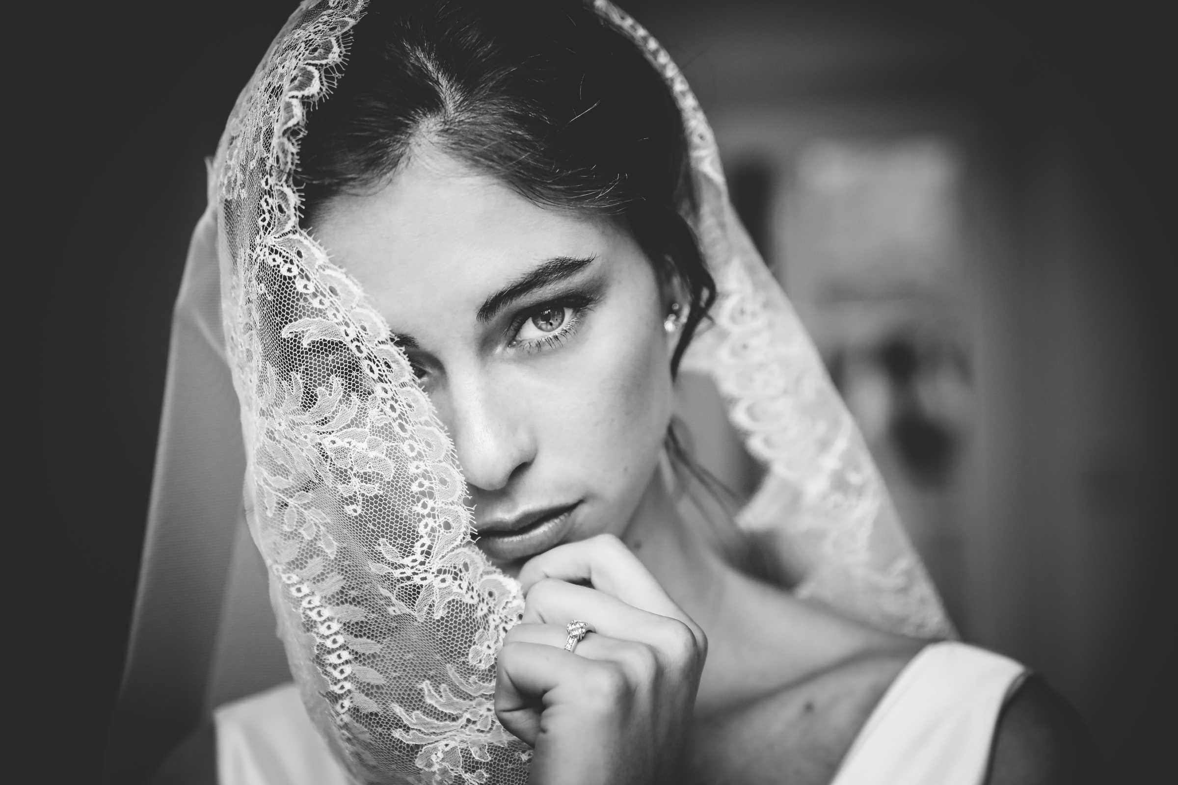 Portrait of bride peeking from behind veil - photo by Julien Laurent-Georges
