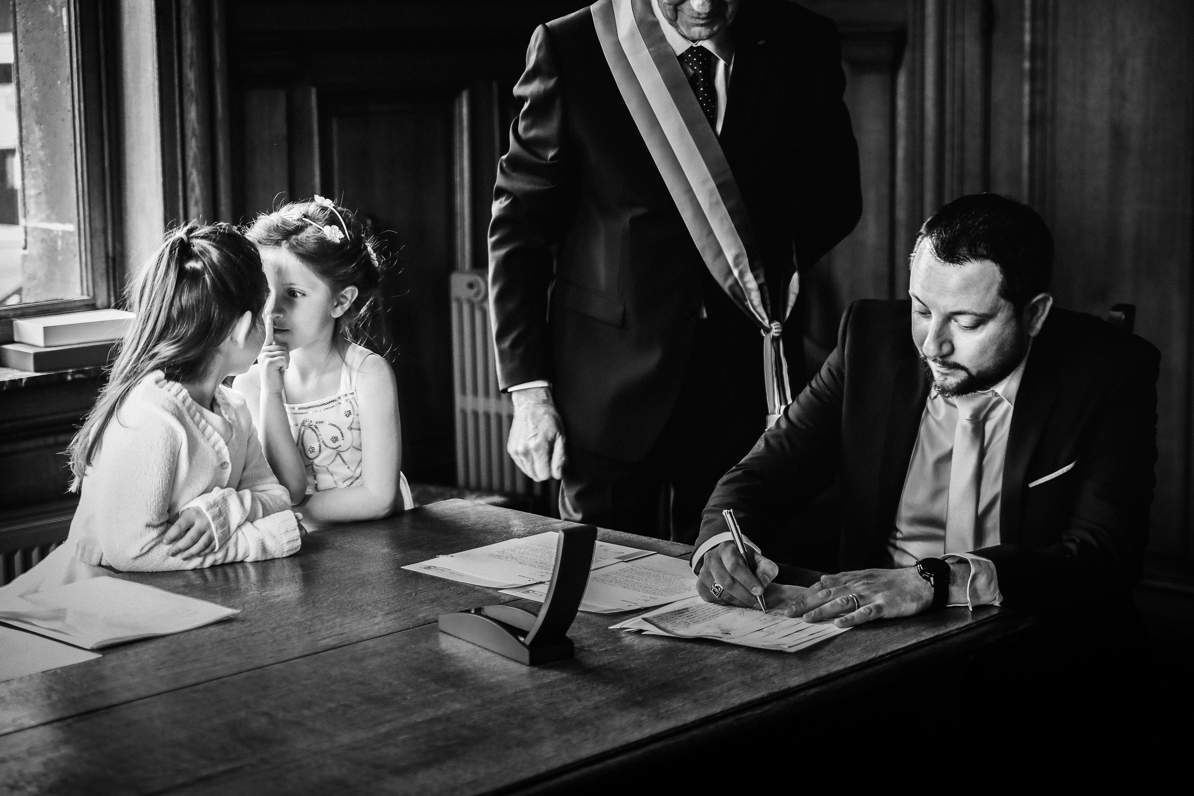 Two kids stand face to face while groom signs wedding certificate - photo by Julien Laurent-Georges