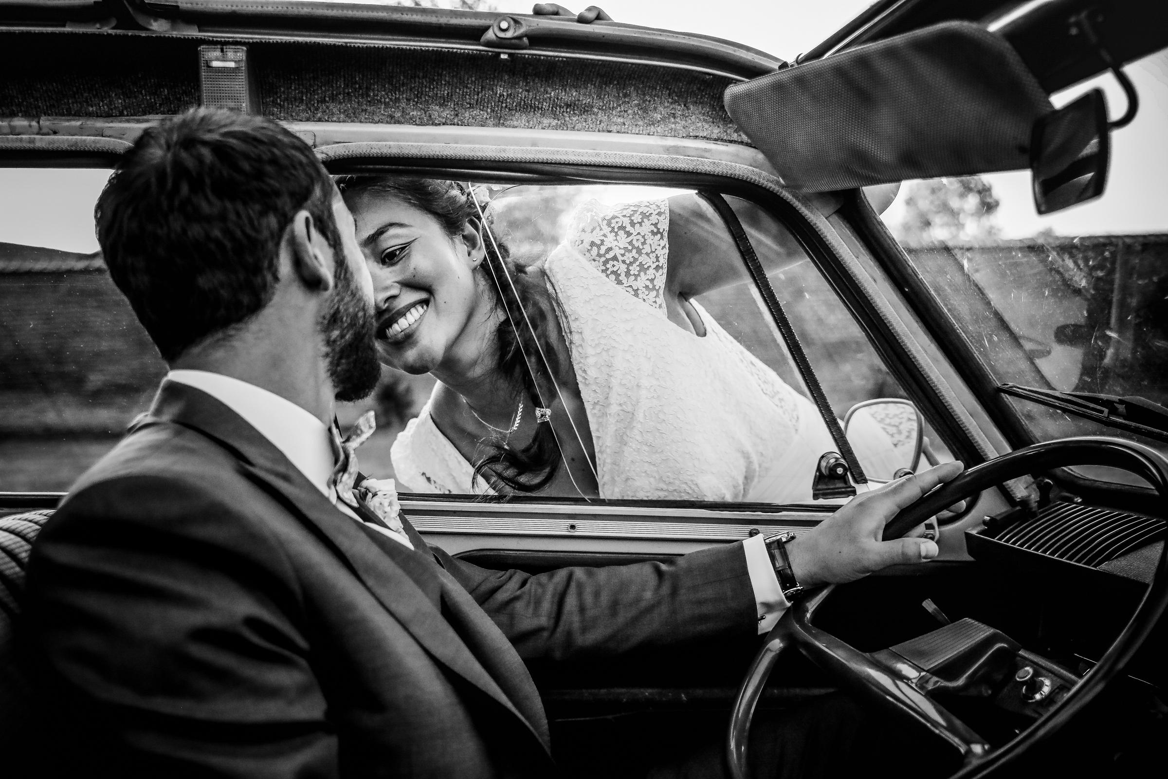 Smiling bride kisses groom through car window - photo by Julien Laurent-Georges