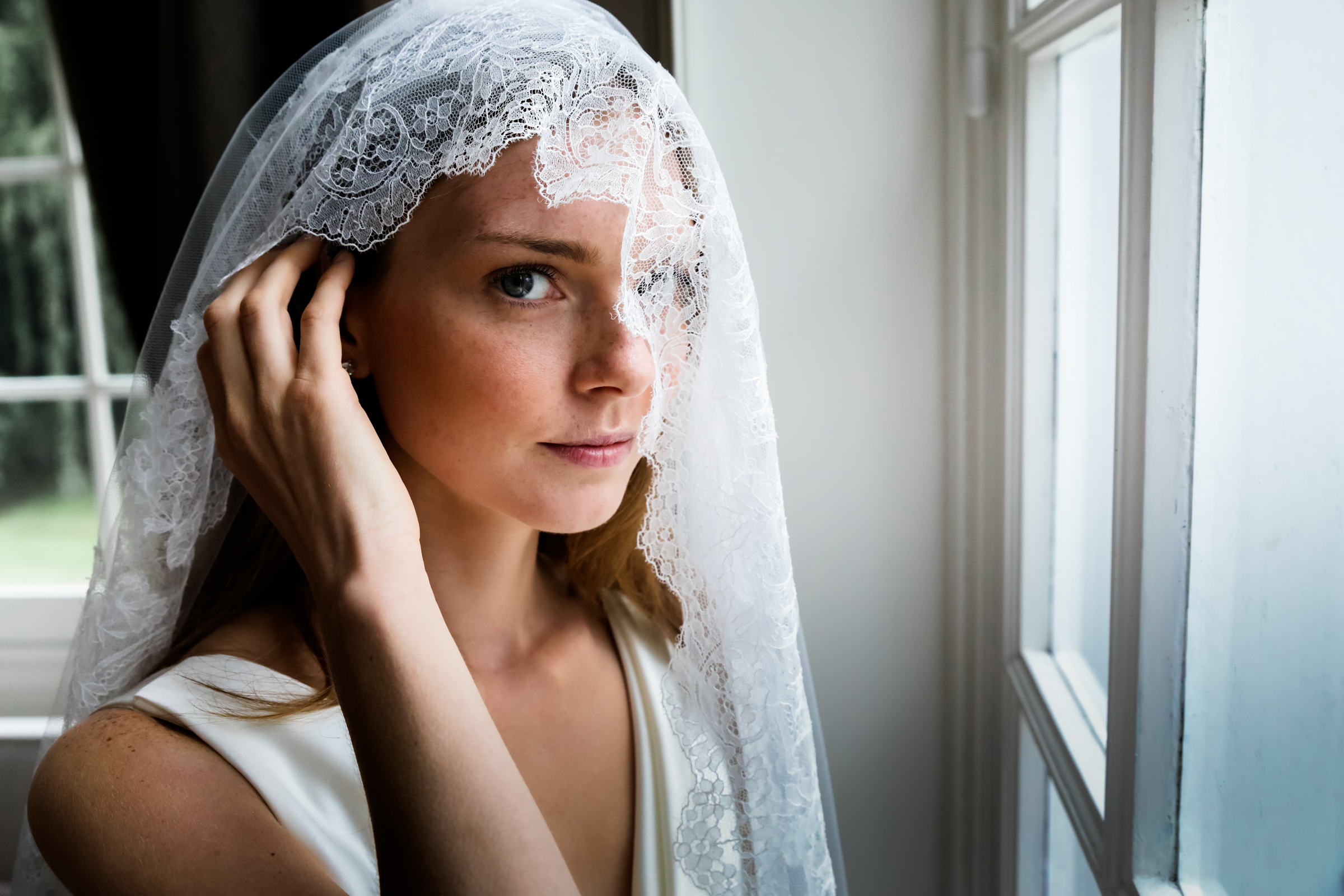 Bride peeks out from lace veil - photo by Julien Laurent-Georges