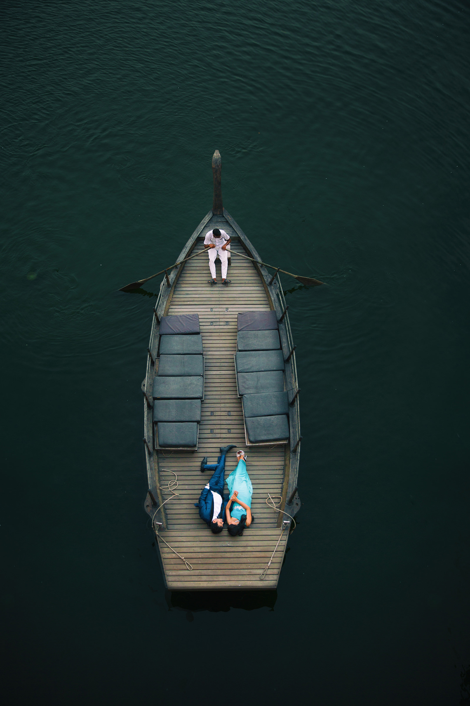 Drone photo of couple being rowed in wooden boat - photo by Shutterink Photography