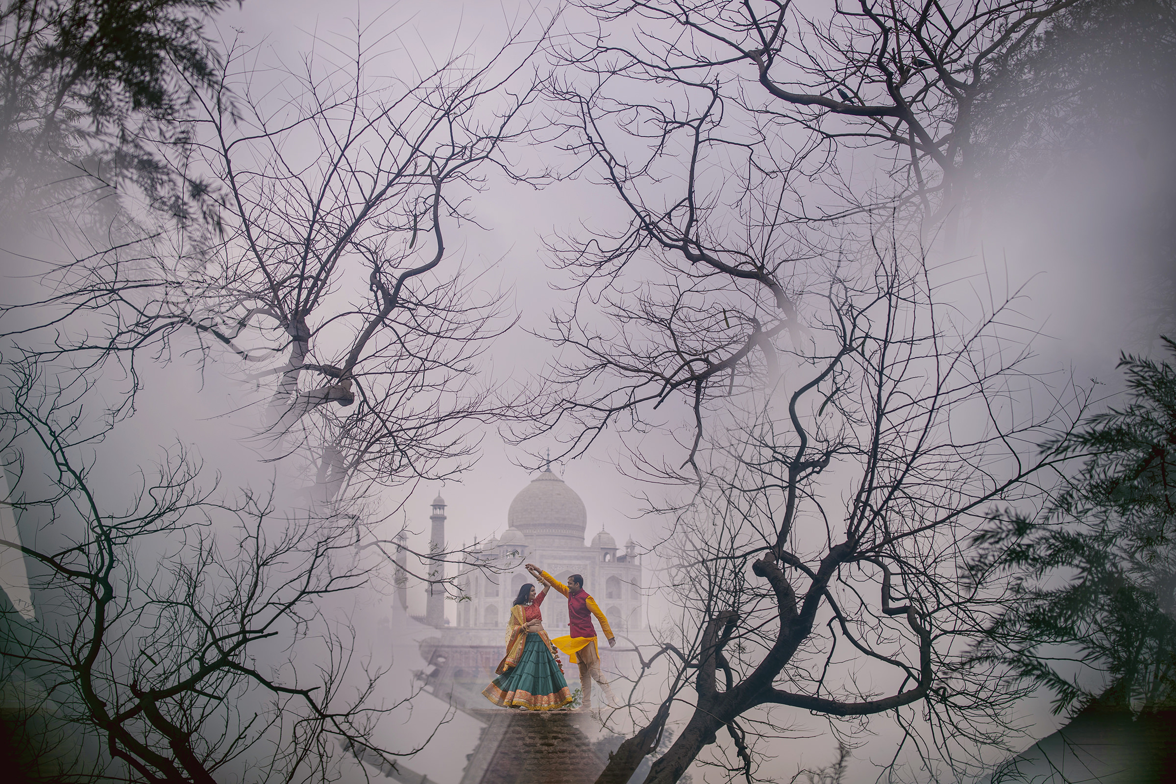 Creative composition of bride and groom against trees and taj mahal - photo by Shutterink Photography