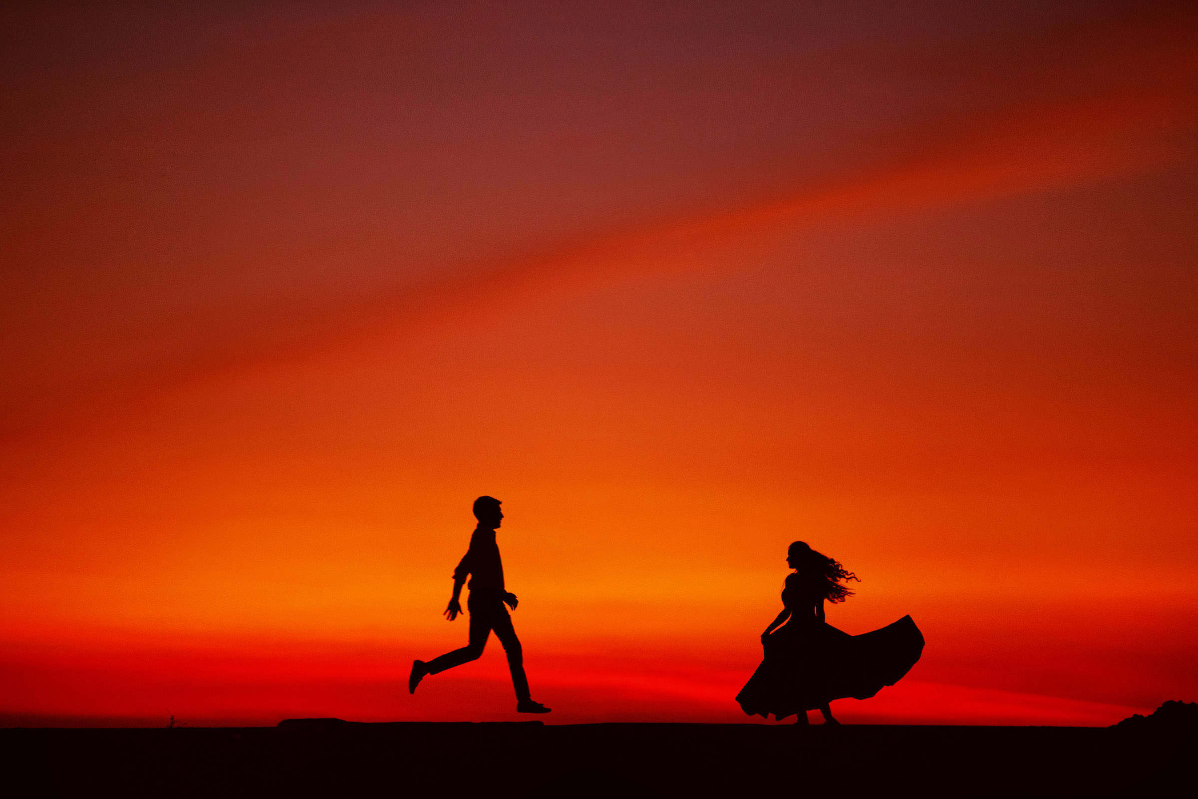 Sunset silhouette of couple running towards each other - photo by Shutterink Photography