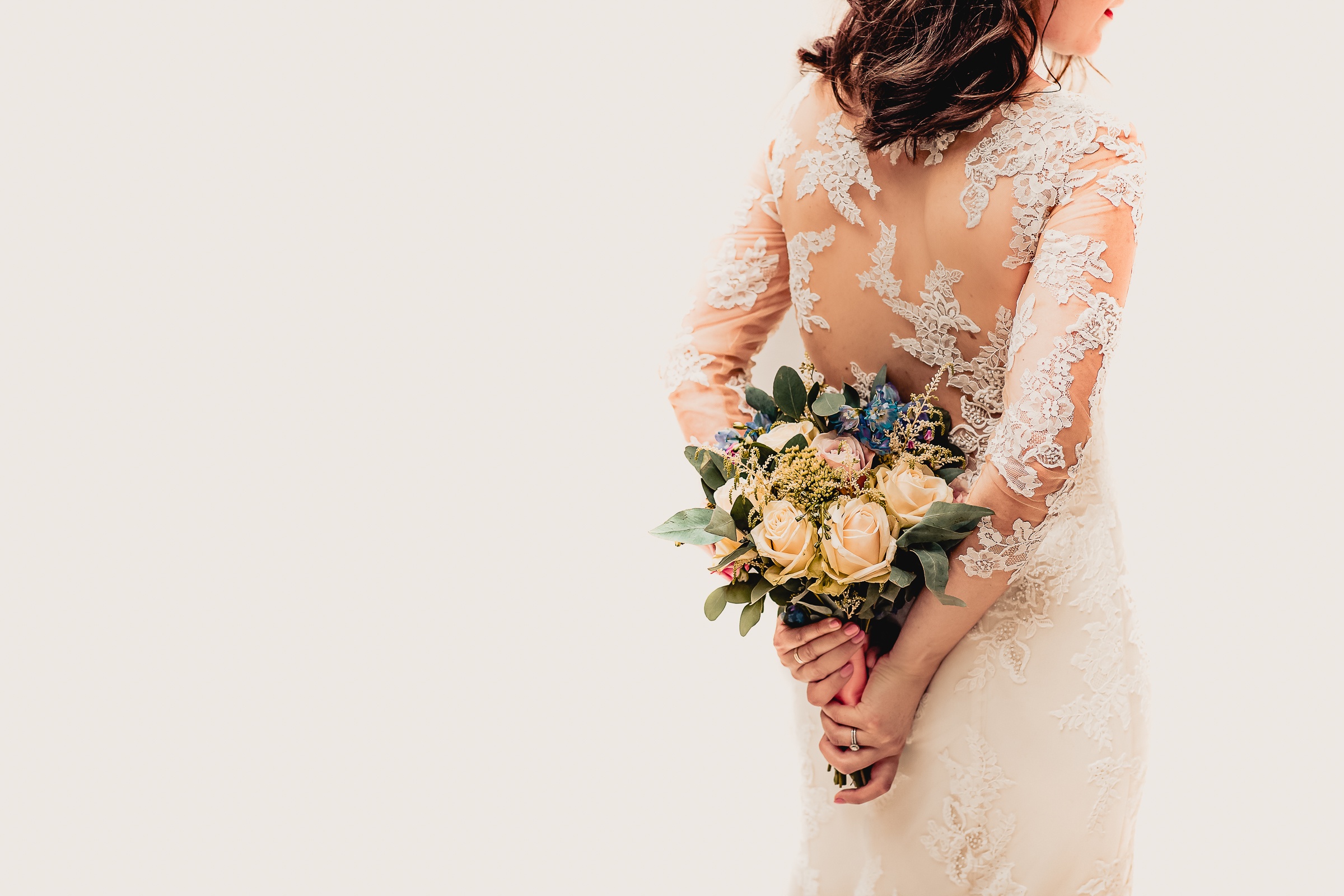 Back of bridal gown with bouquet - photo by Eppel Photography