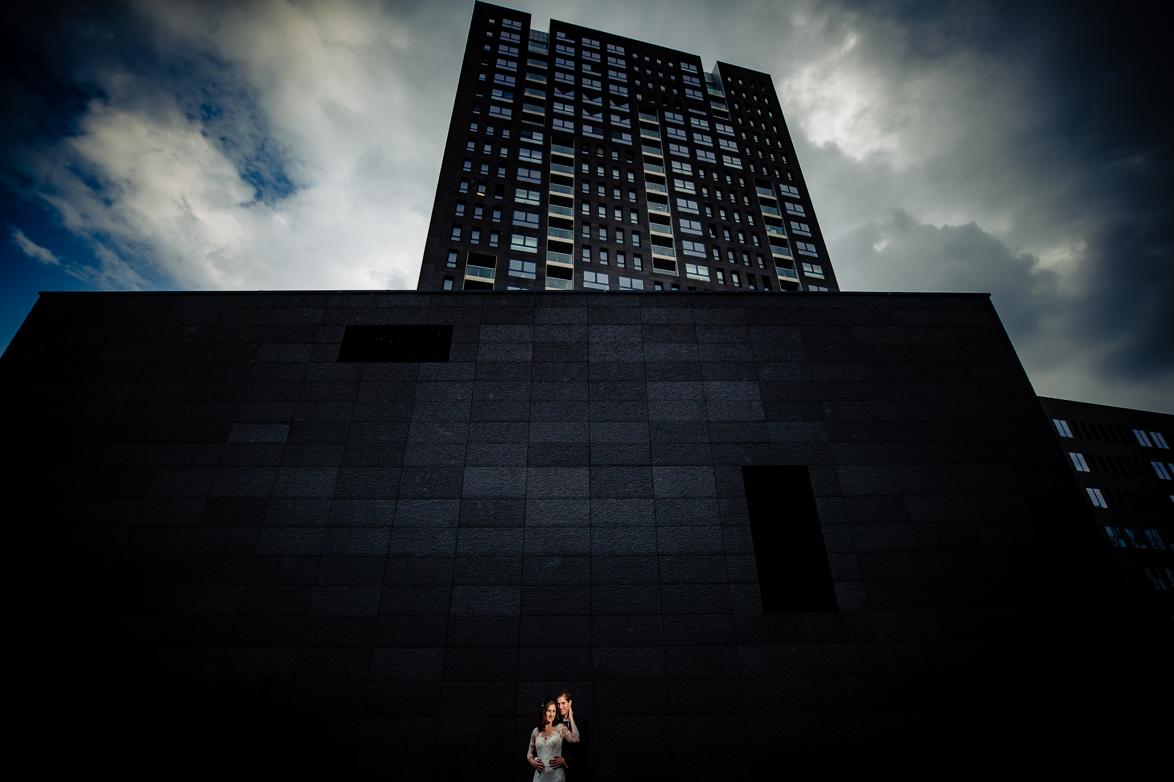 Bride and groom against stark architecture - photo by Eppel Photography
