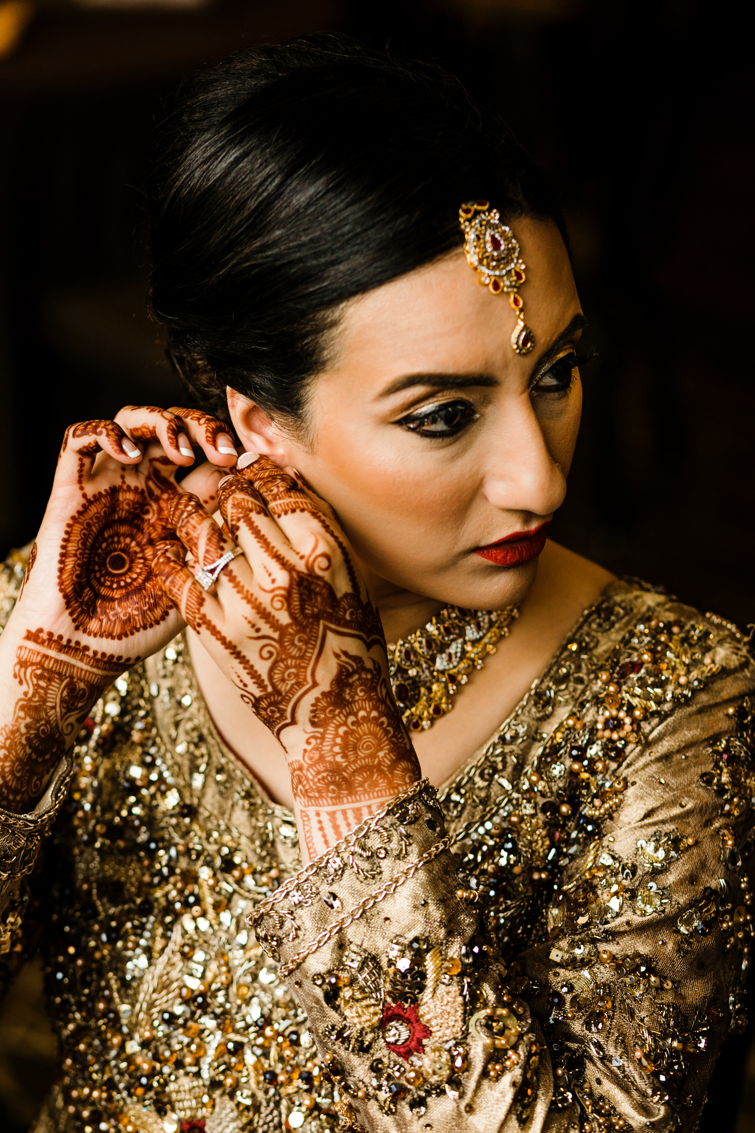 Bride fastening earring with henna hands - photo by Alante Photography