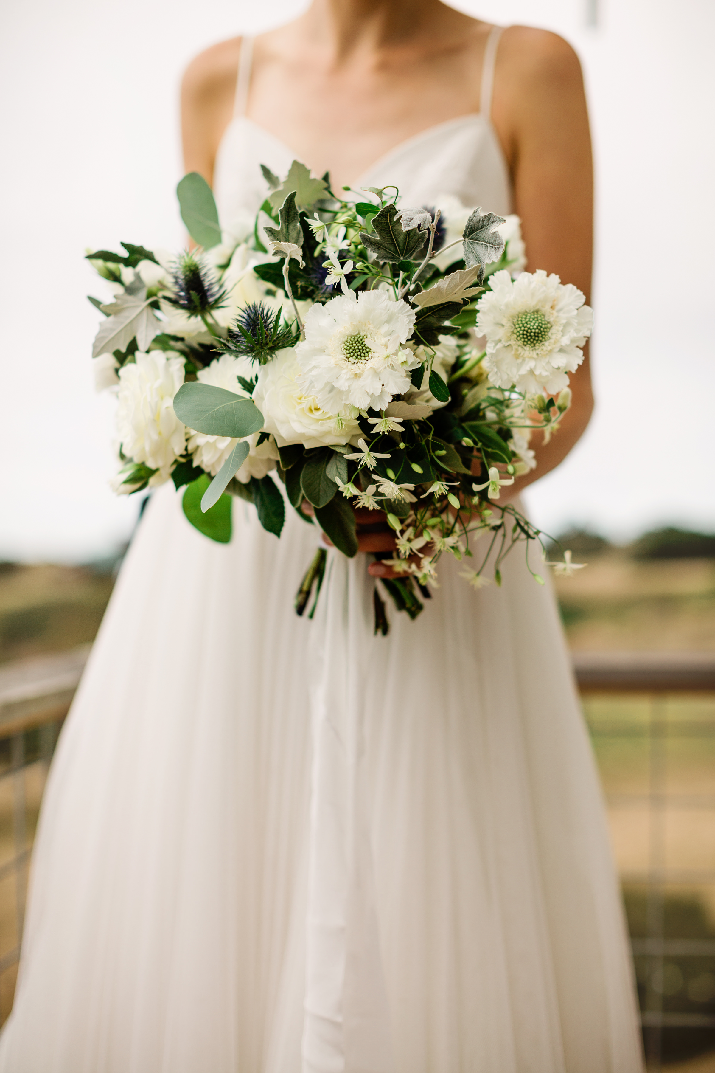 Bride in sleeveless aline with white floral bouquet - photo by Alante Photography