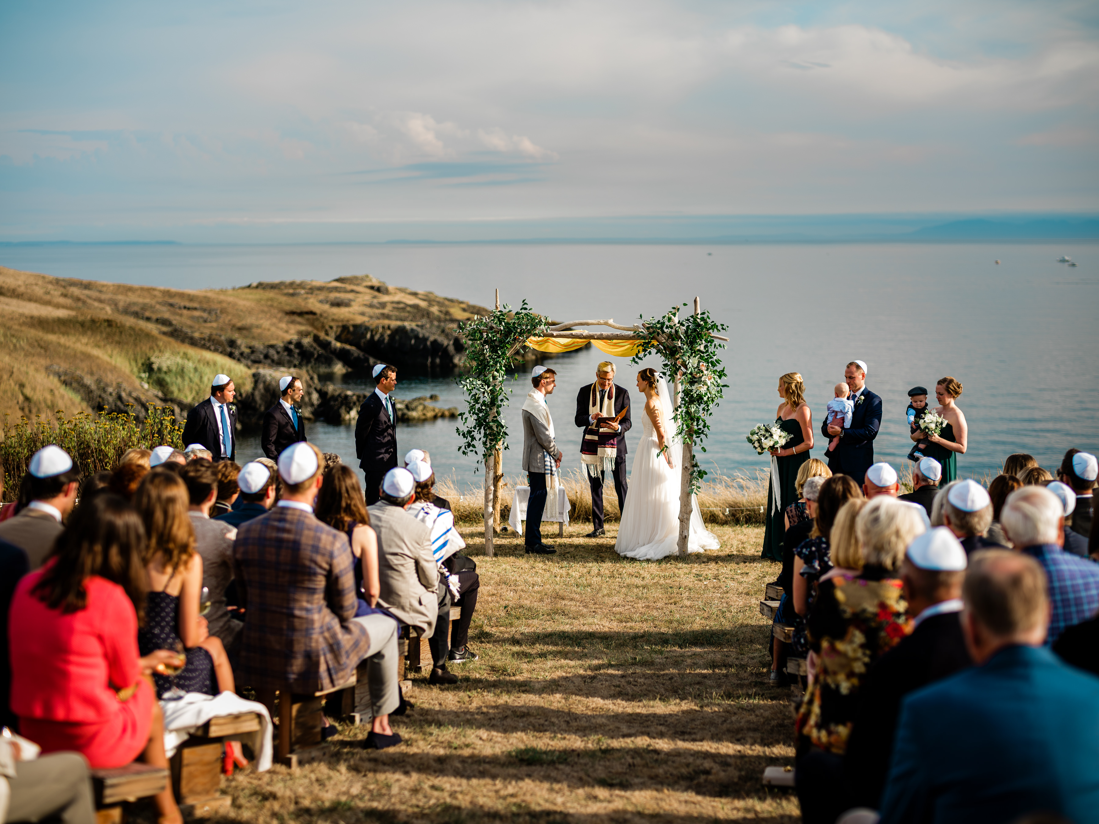 Guests seated at ceremony under seaside chuppah - photo by Alante Photography