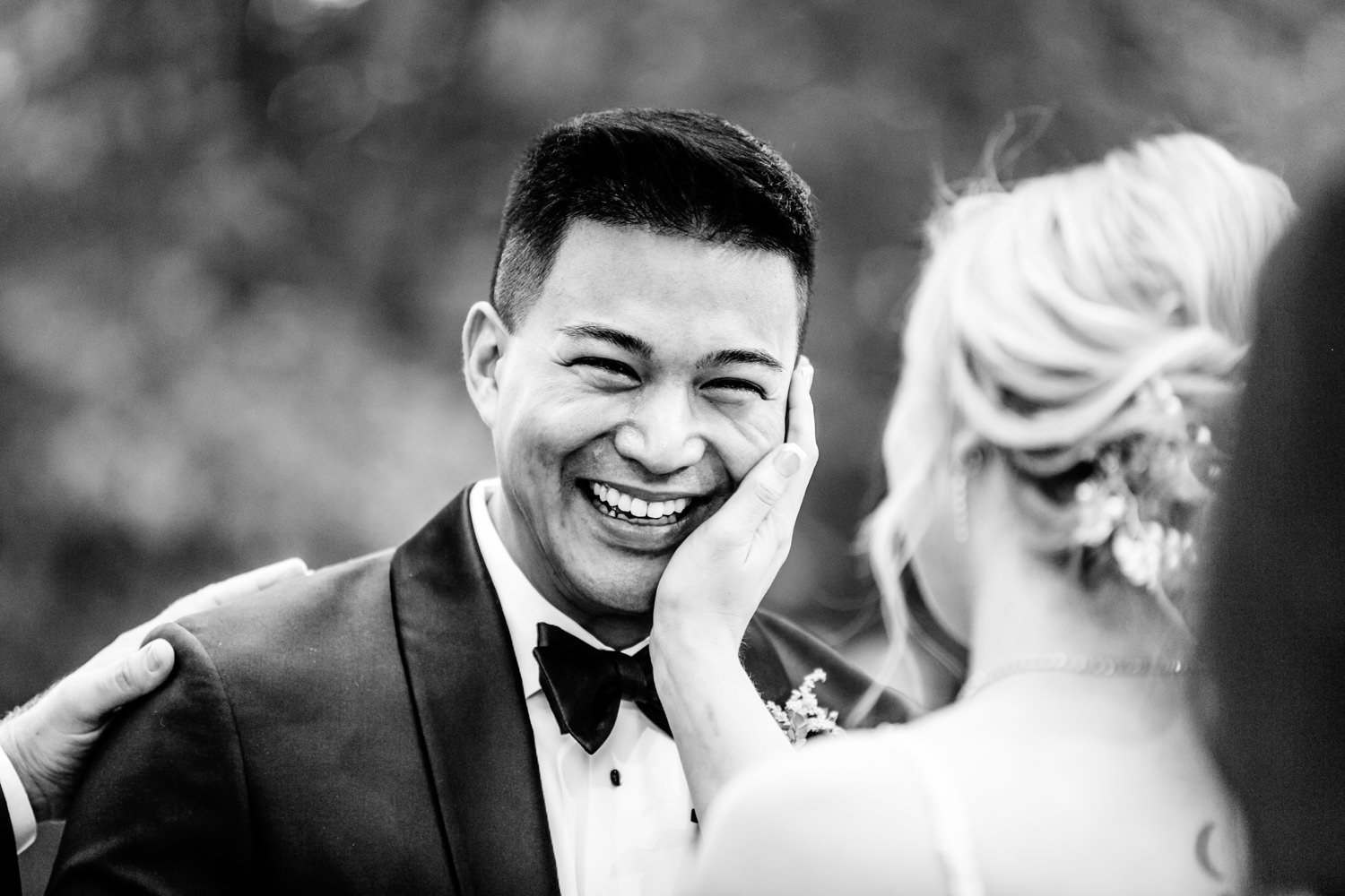Bride touches cheek of smiling groom - photo by AL Gawlik Photography