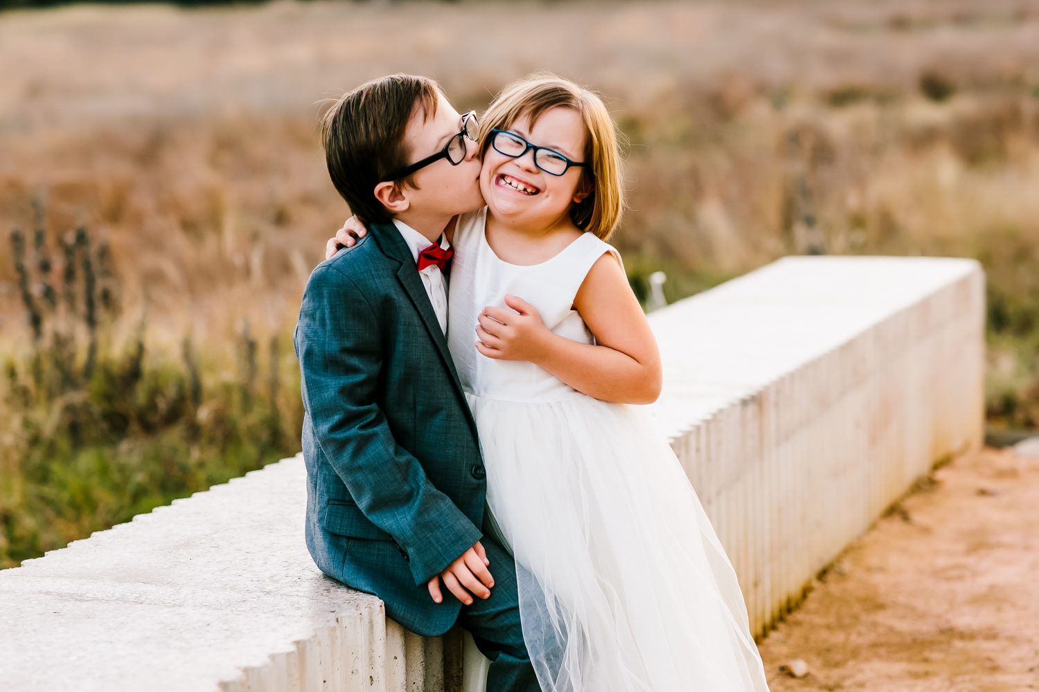 Funny portrait of boy kissing girl - photo by AL Gawlik Photography