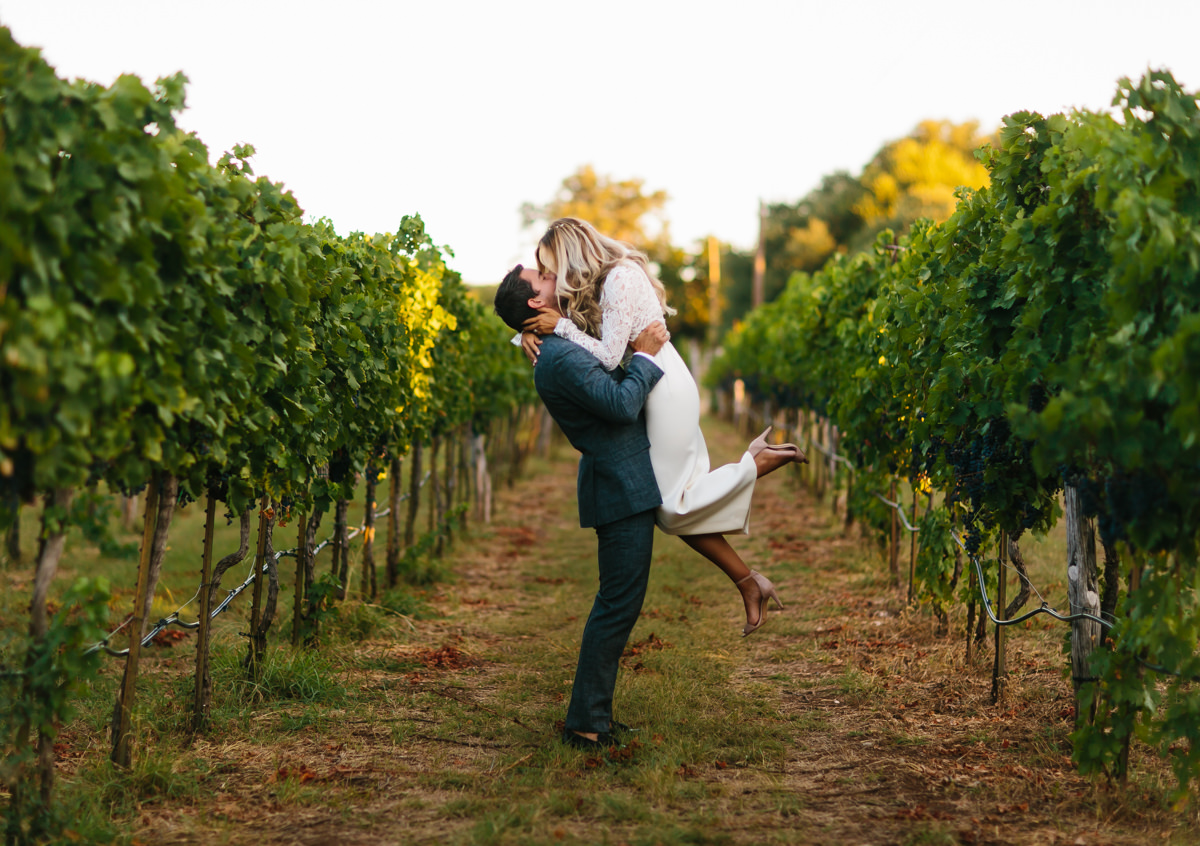 Groom lifts bride off her feet in vineyard - photo by AL Gawlik Photography