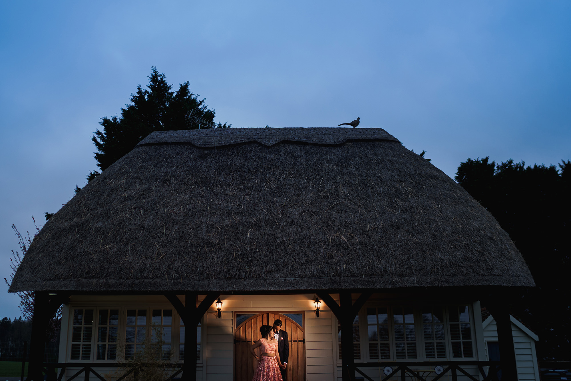 Couple outside Quendon Parklands thatched roof cottage - photo by F5 Photography