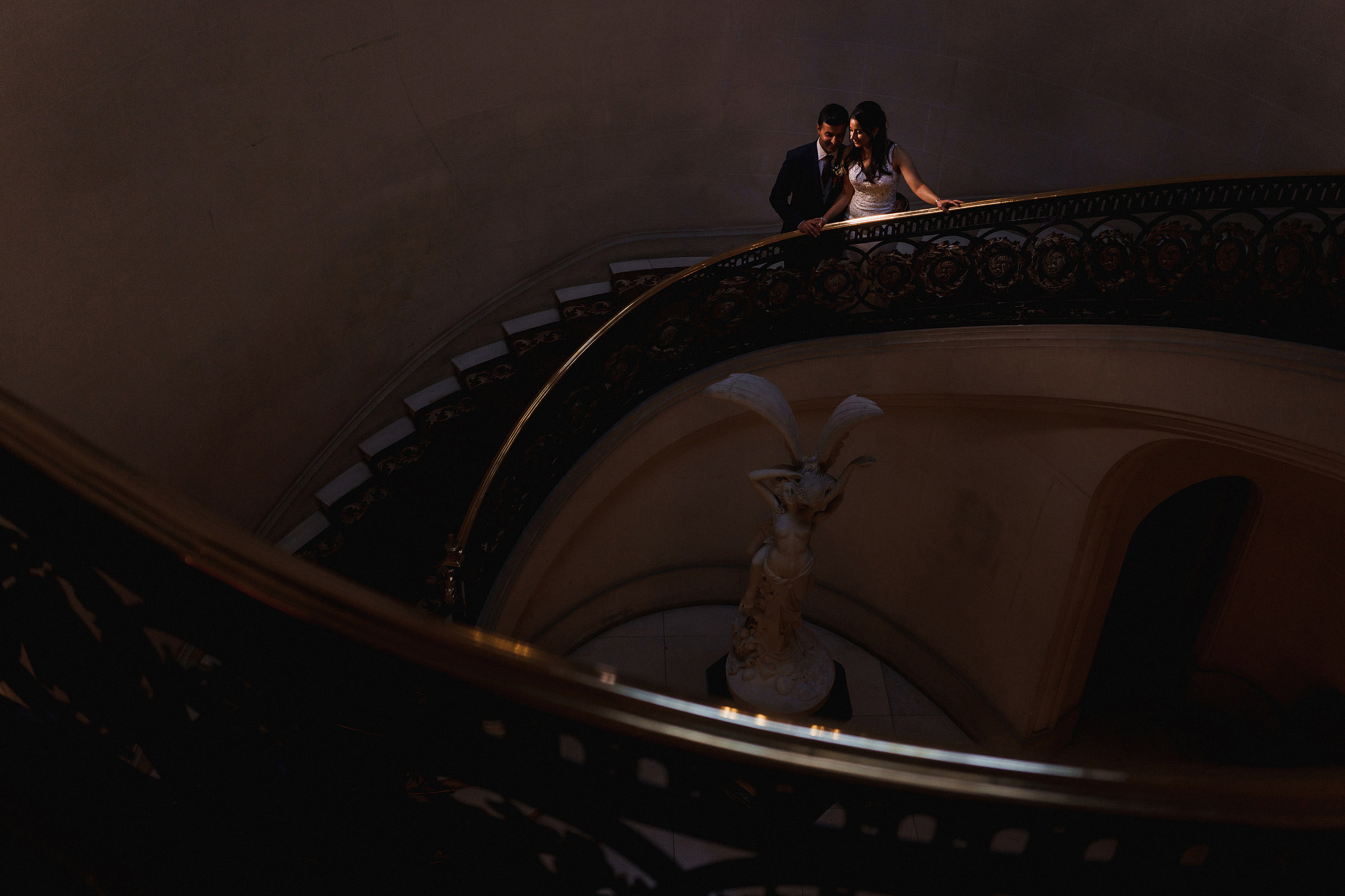 Couple on sweeping spiral staircase - photo by f5 Photography