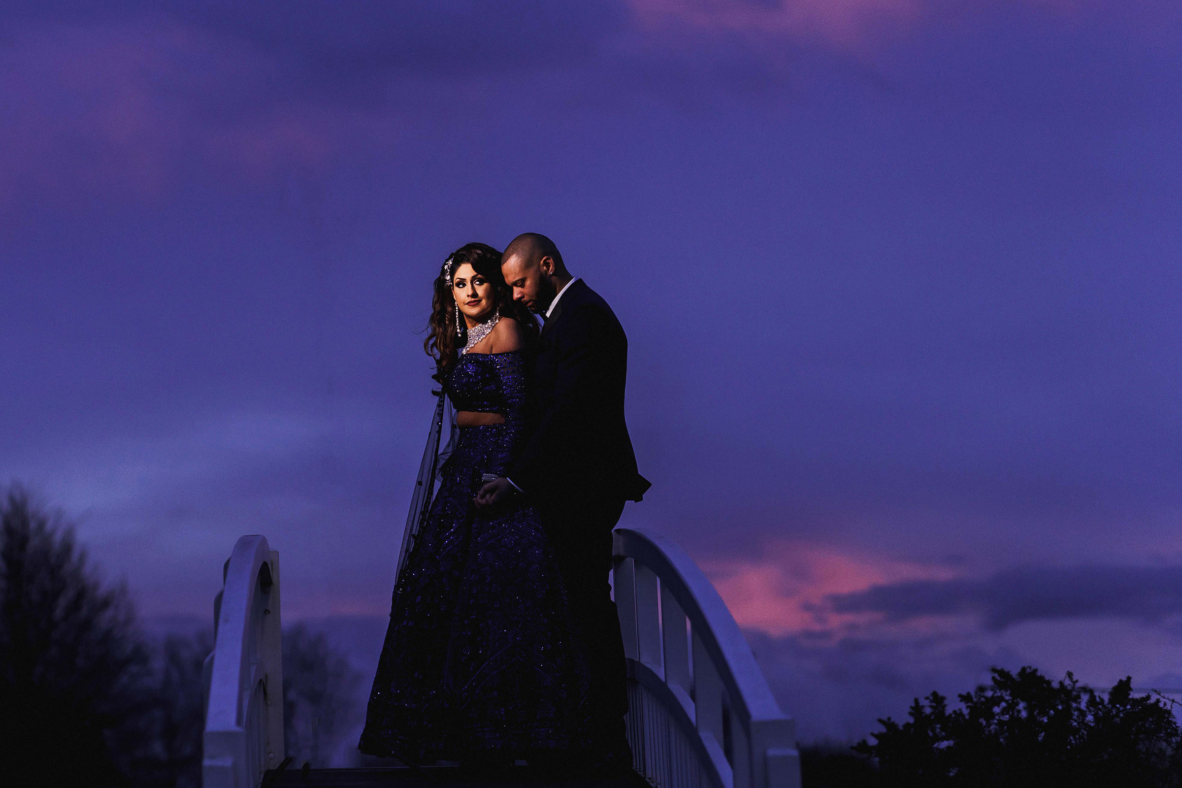 Dramatic couple portrait against purple sky - photo by f5 Photography