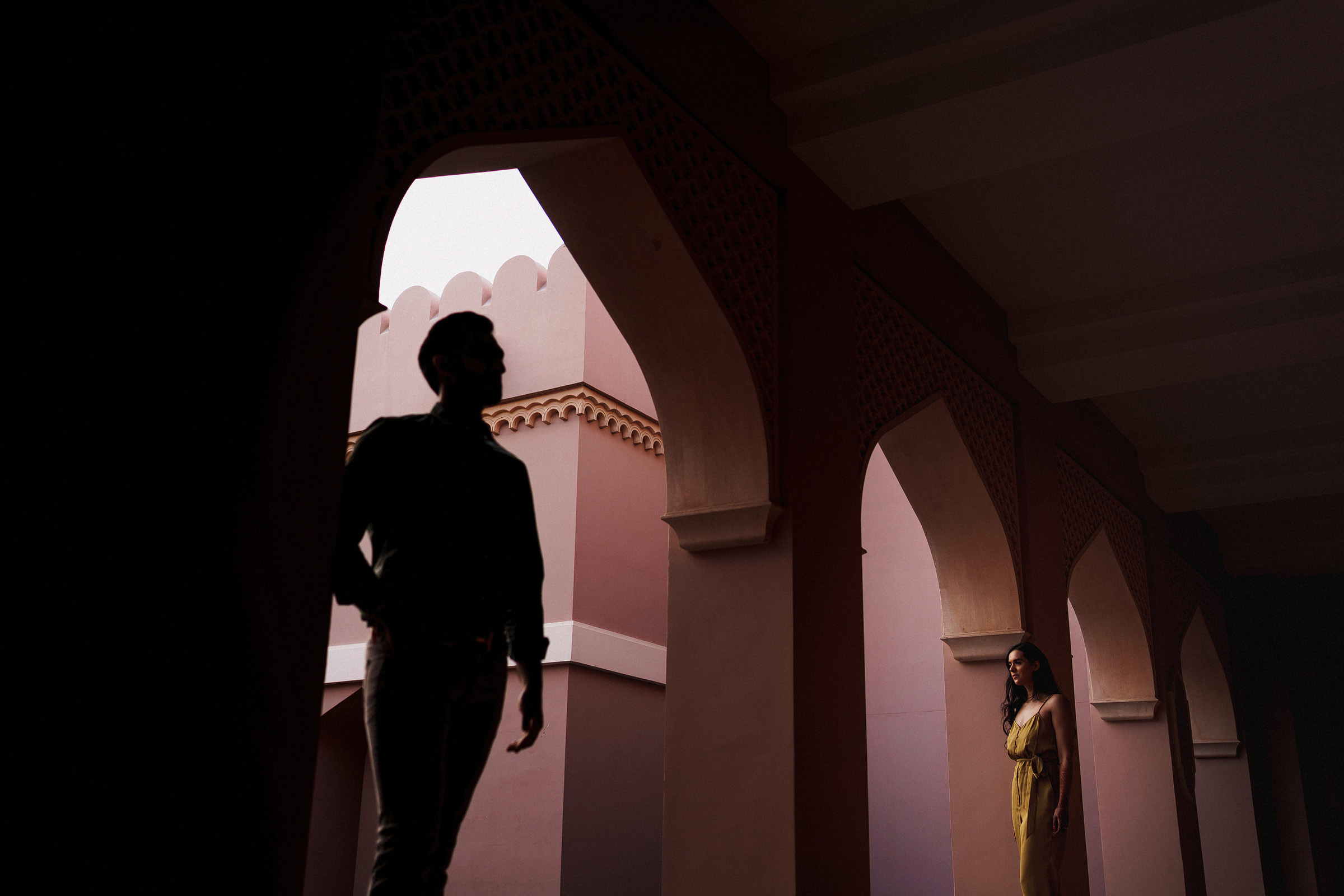 Groom silhouette with bride amid pink archways - photo by f5 Photography