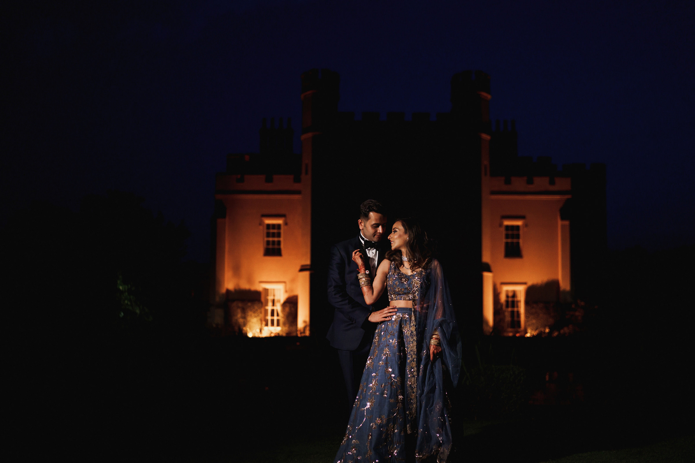 Indian couple at night against Ditton Manor Slough venue  - photo by F5 Photography