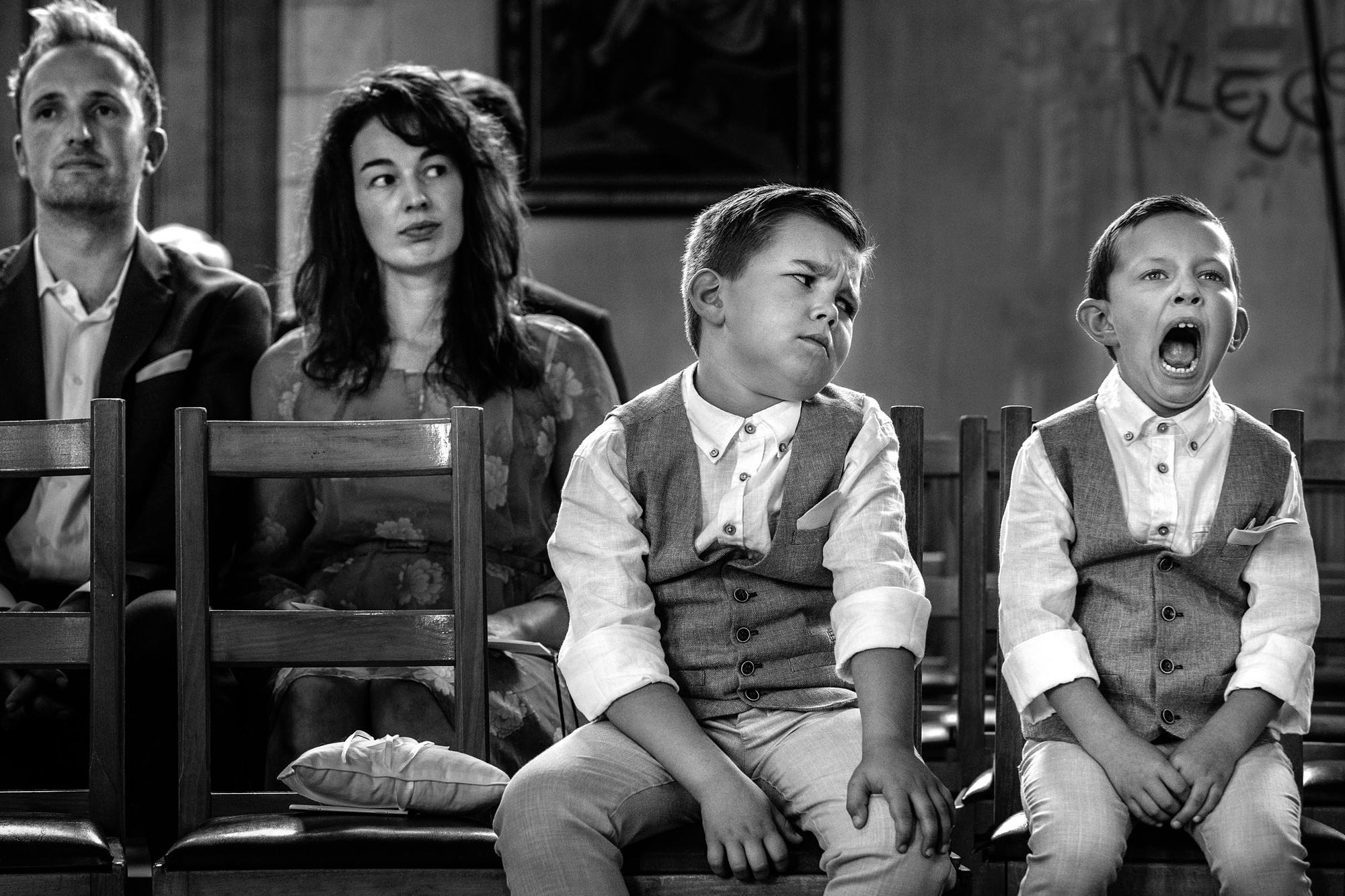 Hilarious photo of little boy yawning at wedding with brother disapproving  by Yves Schepers - Belgium wedding photographer