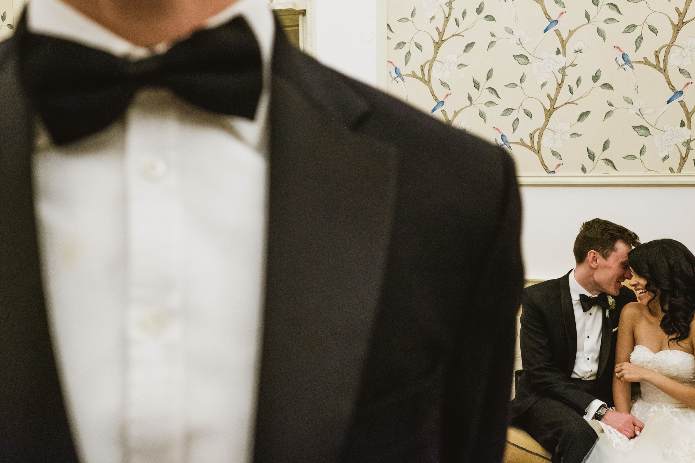 Bride and groom whisper in the background - photo by York Place Studios