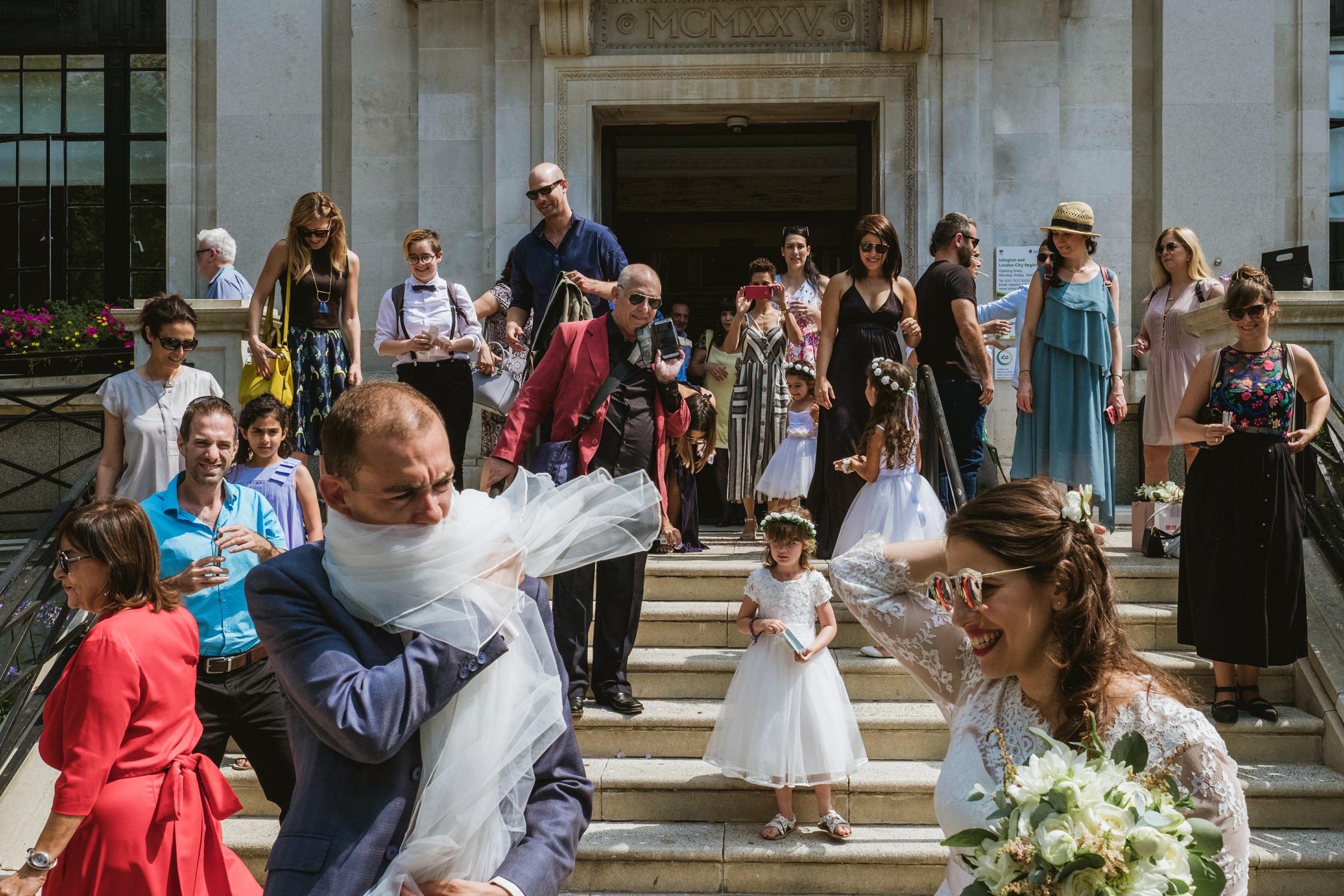 Groom wraps himself in veil amidst onlookers - photo by York Place Studios