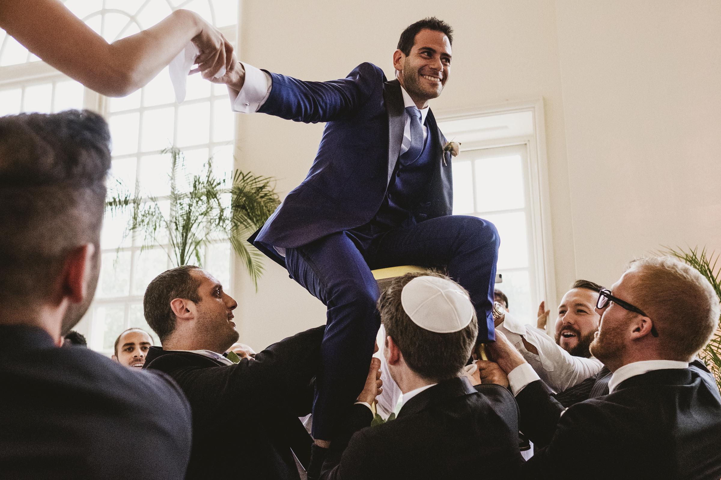 Groom aloft at Jewish wedding - photo by York Place Studios