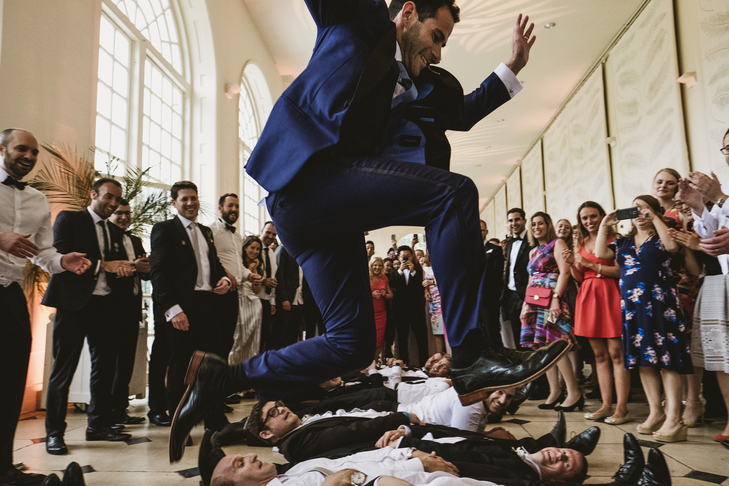 Groom leaping over prone guests at Kew Gardens UK - photo by York Place Studios