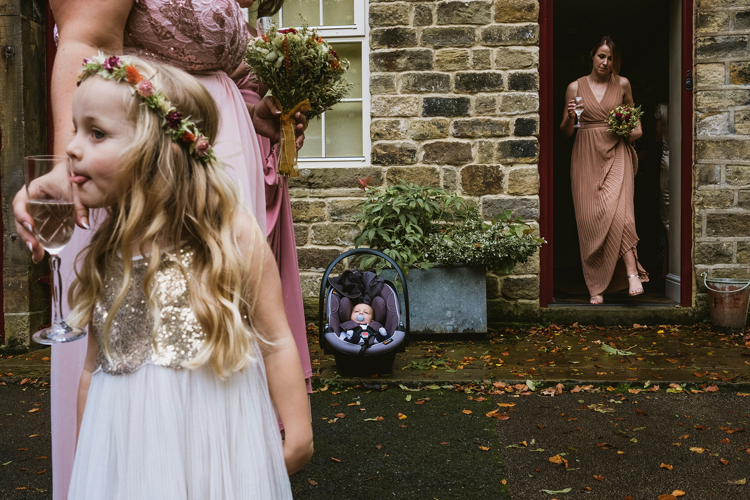 Funny scene of flower girl with bridesmaids with wine glasses - photo by York Place Studios
