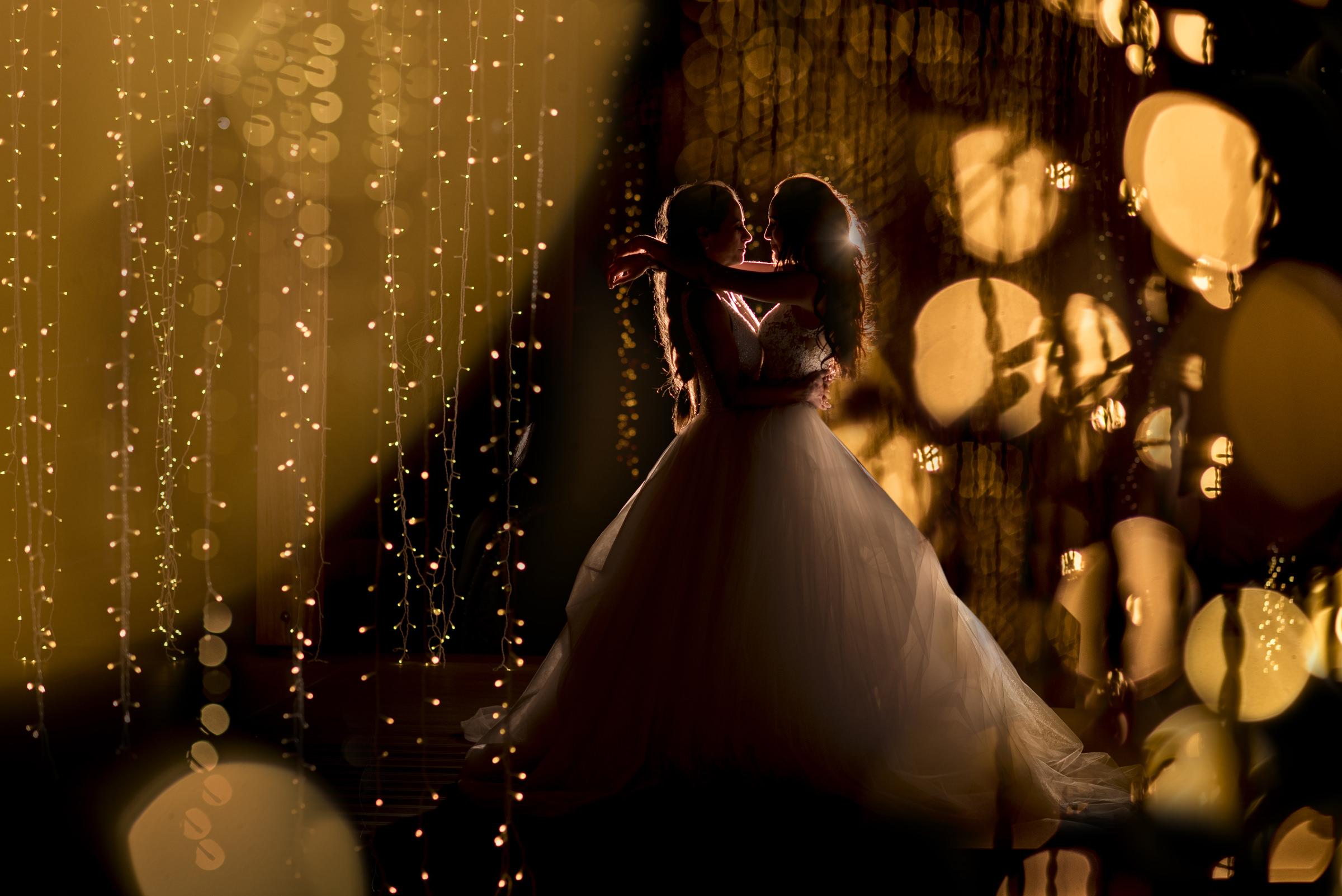 Bokeh portrait of two brides in princess dresses - photo by Jacki Bruniquel