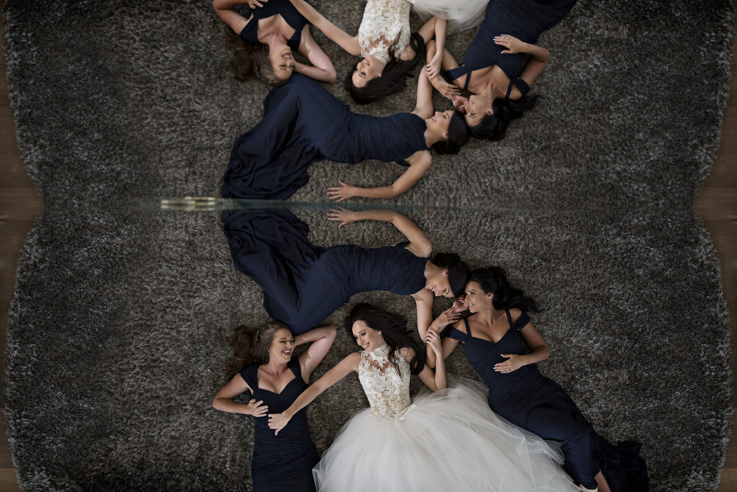 Bride and bridesmaids reflected in mirror- photo by Jacki Bruniquel