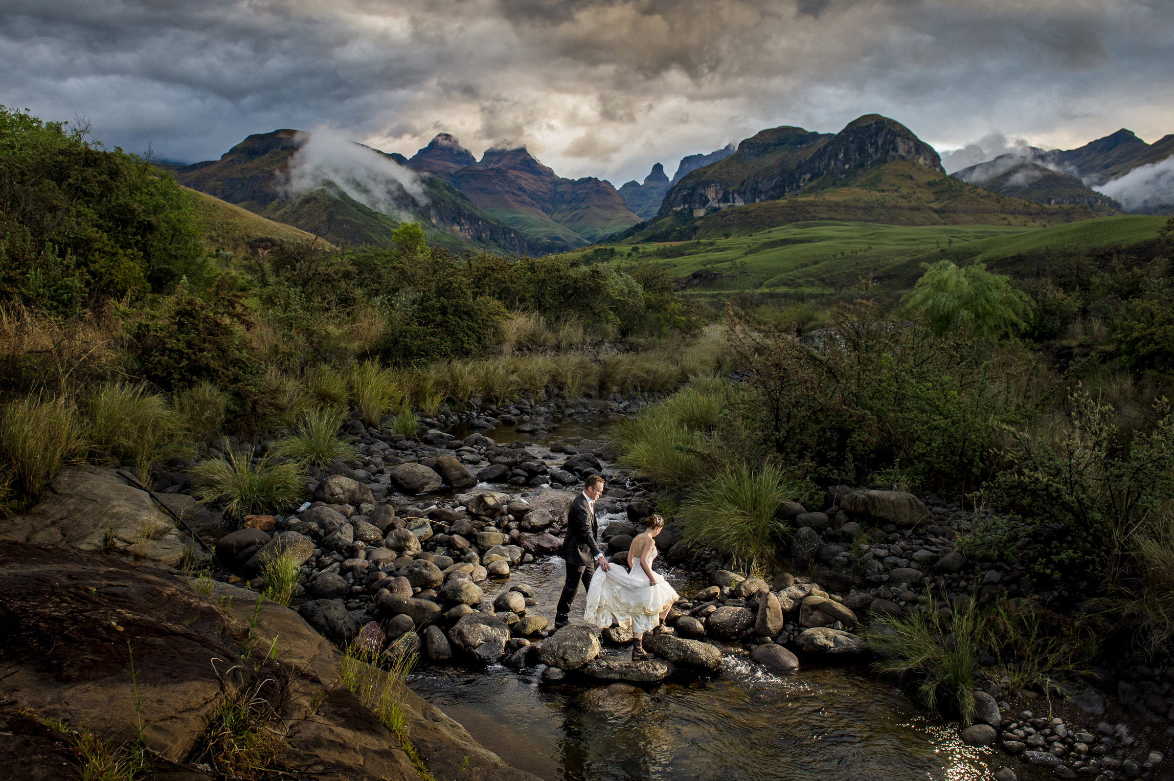 Bride and groom crossing South African river - photo by Jacki Bruniquel