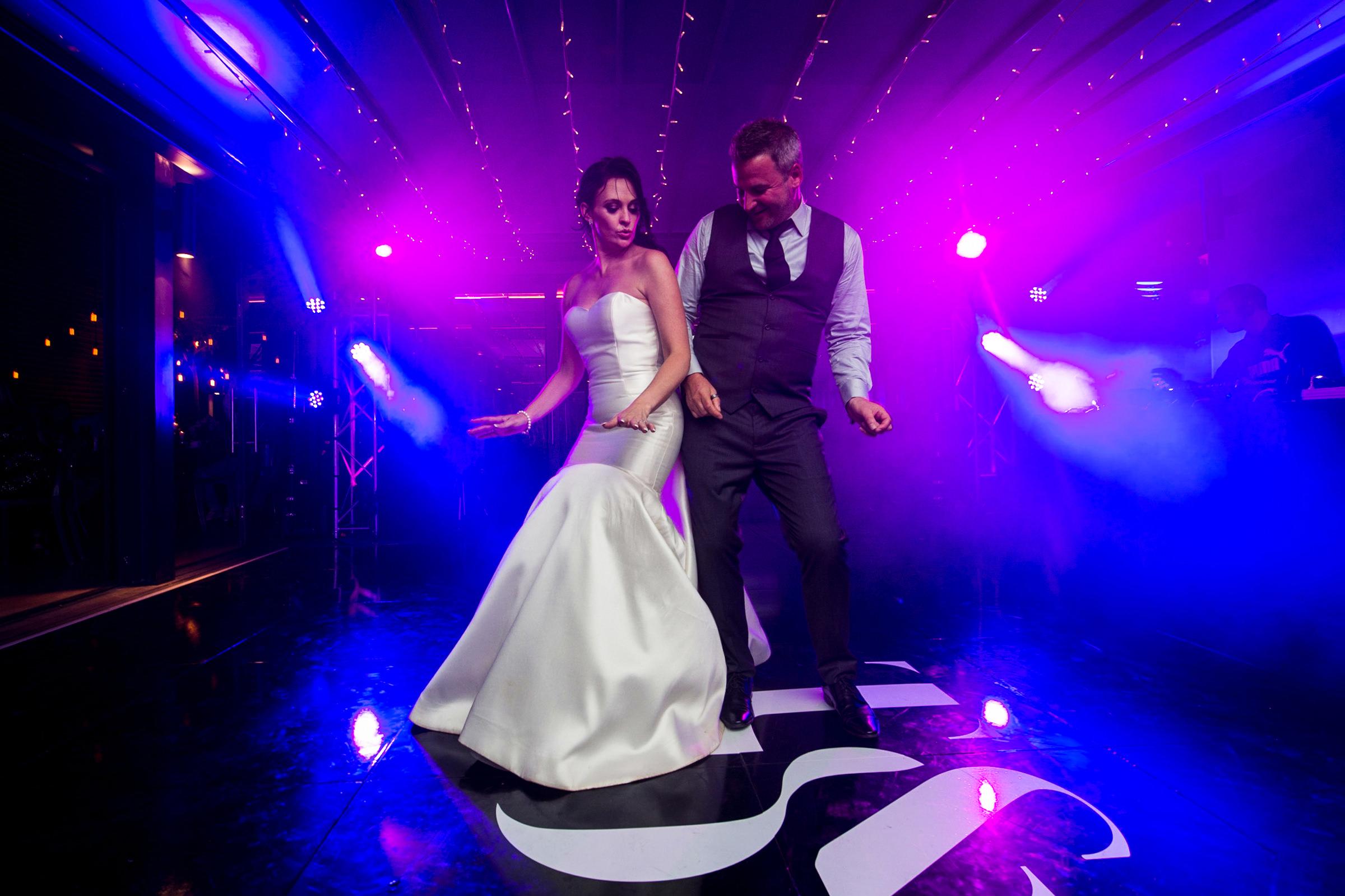 Bride and groom bump on dance floor - photo by Jacki Bruniquel