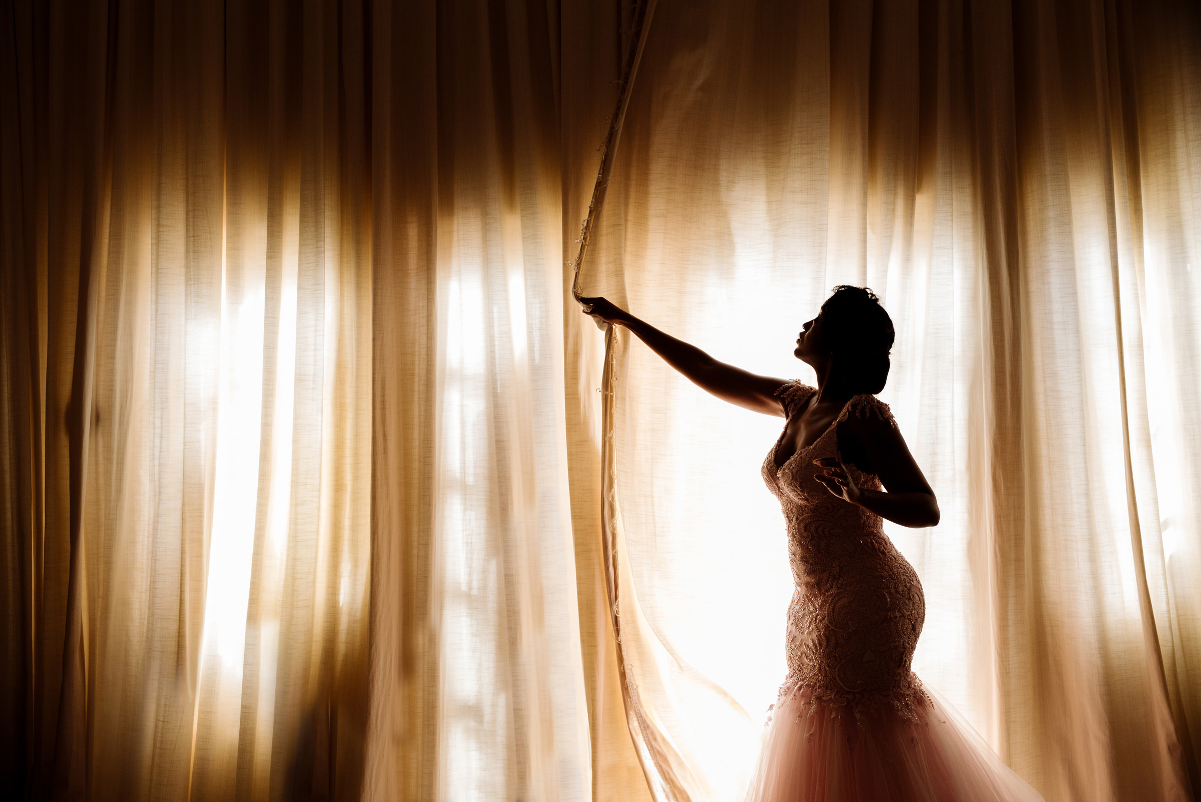 Bride in trumpet gown pulls the drapes before wedding - photo by Jacki Bruniquel
