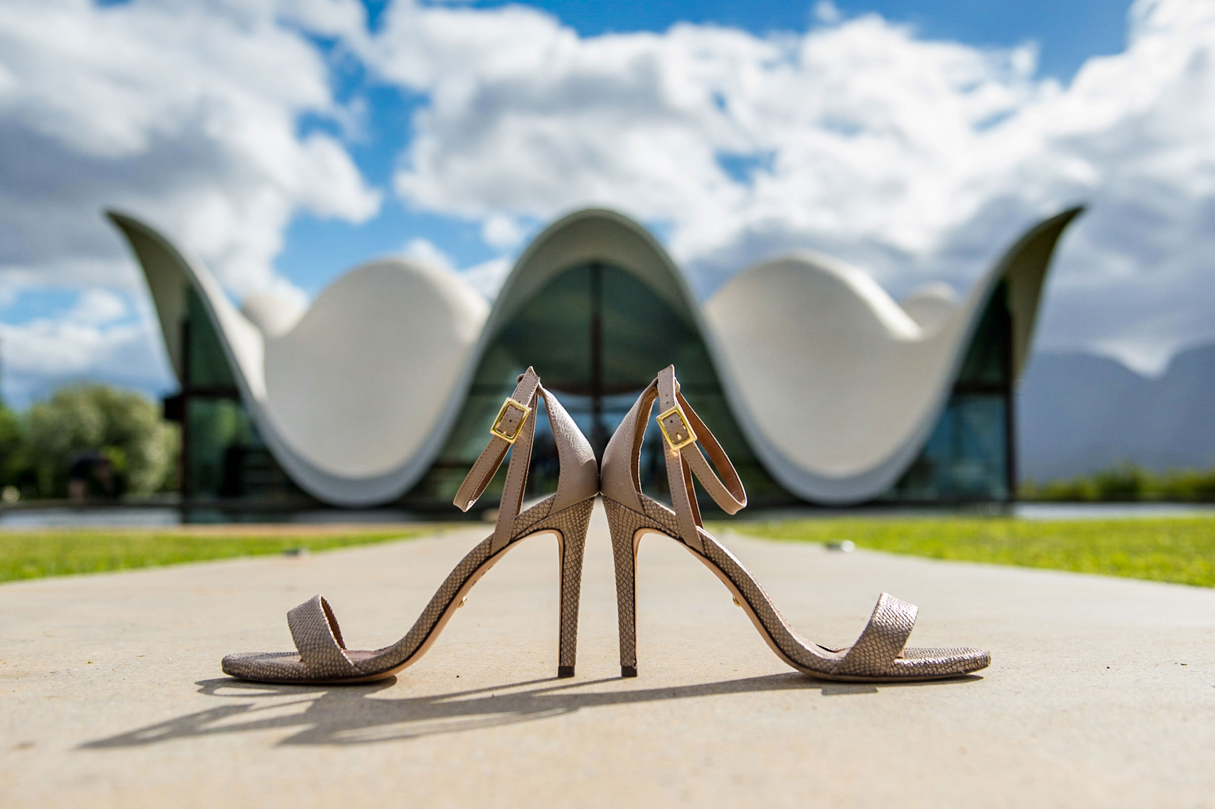 Creative composition of high heel shoes against modern building - photo by Jacki Bruniquel