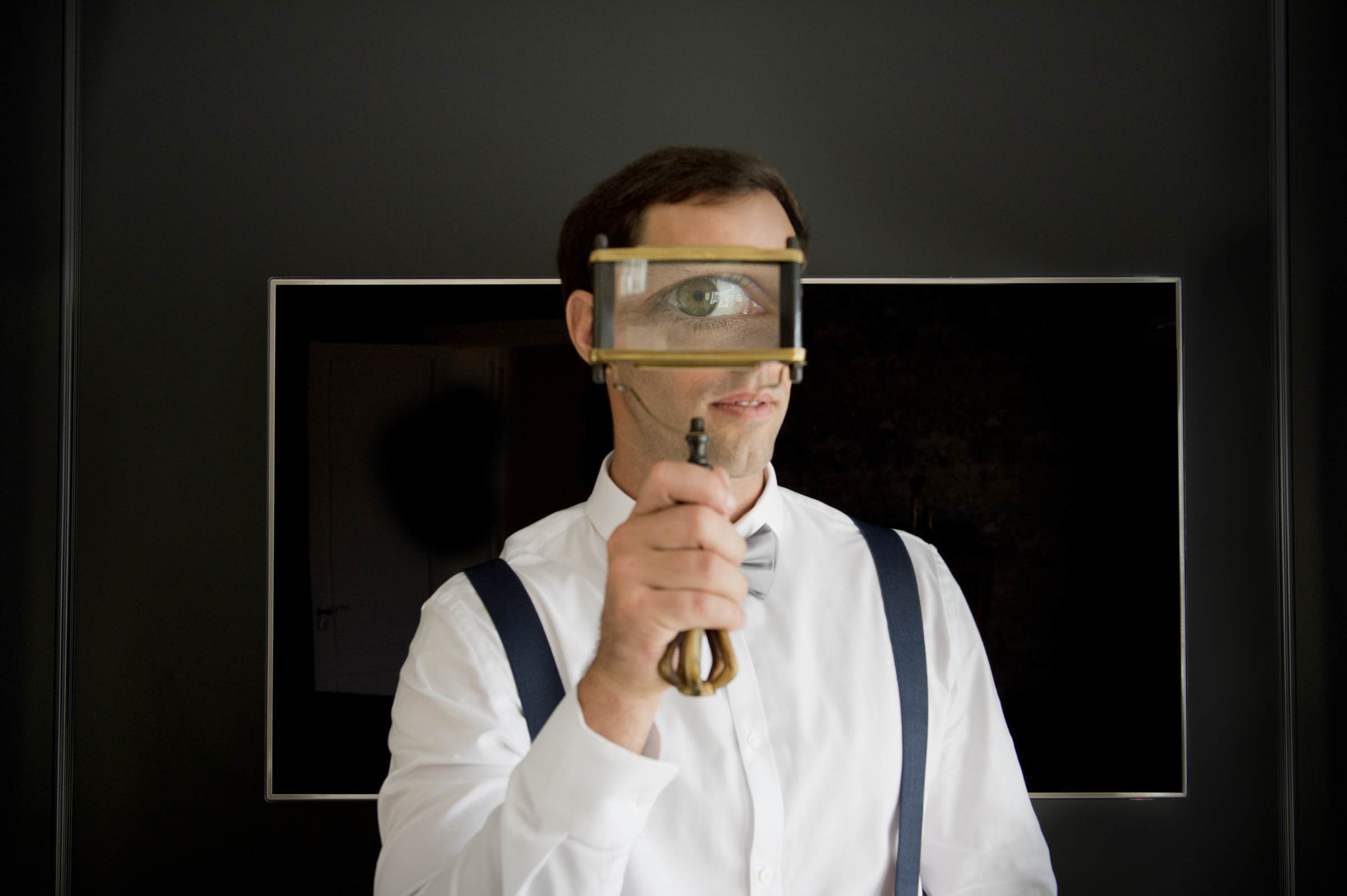 Groom looks with one eye through magnifying glass - photo by Jacki Bruniquel