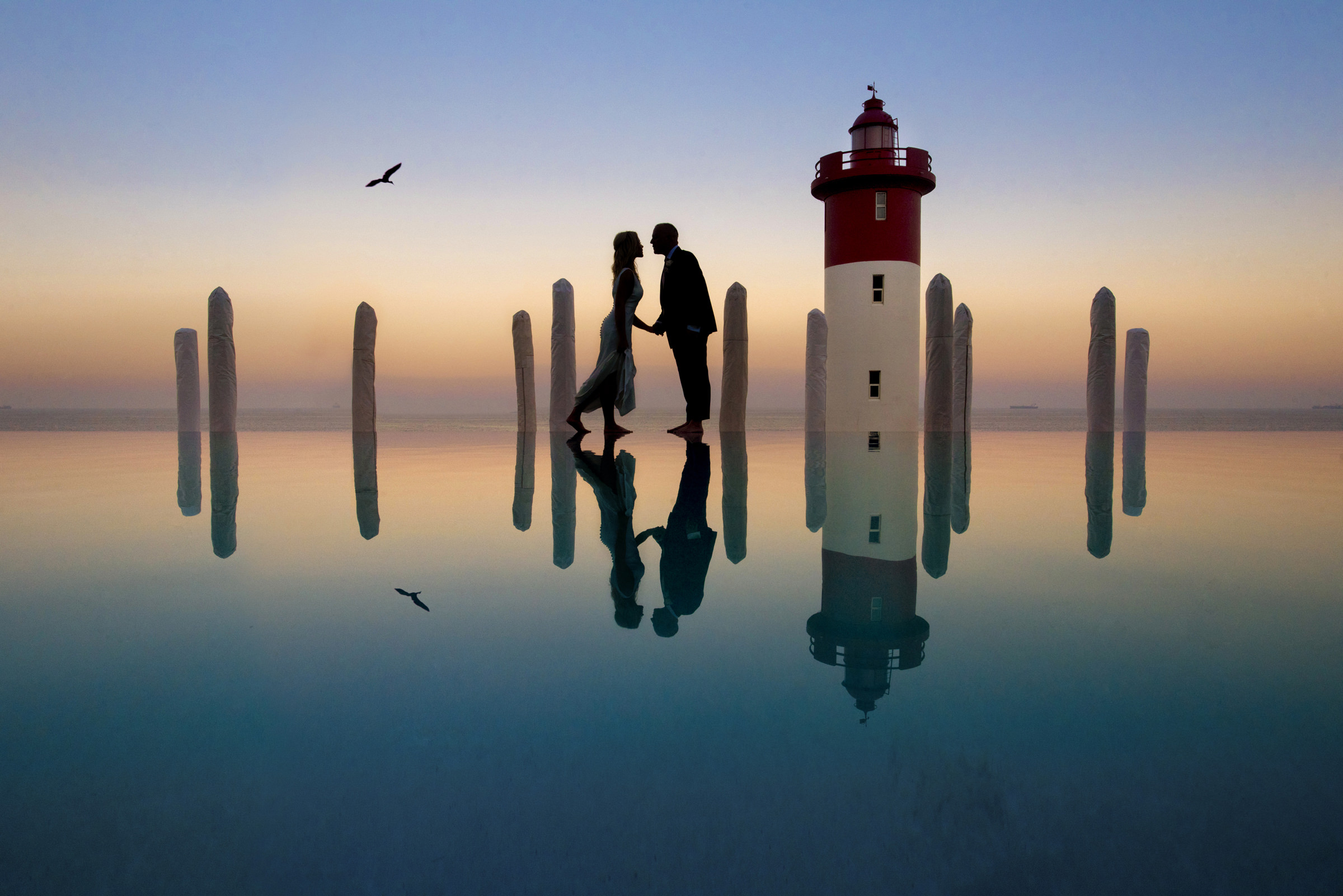 Silhouette of bride and groom kissing while walking on water - photo by Jacki Bruniquel