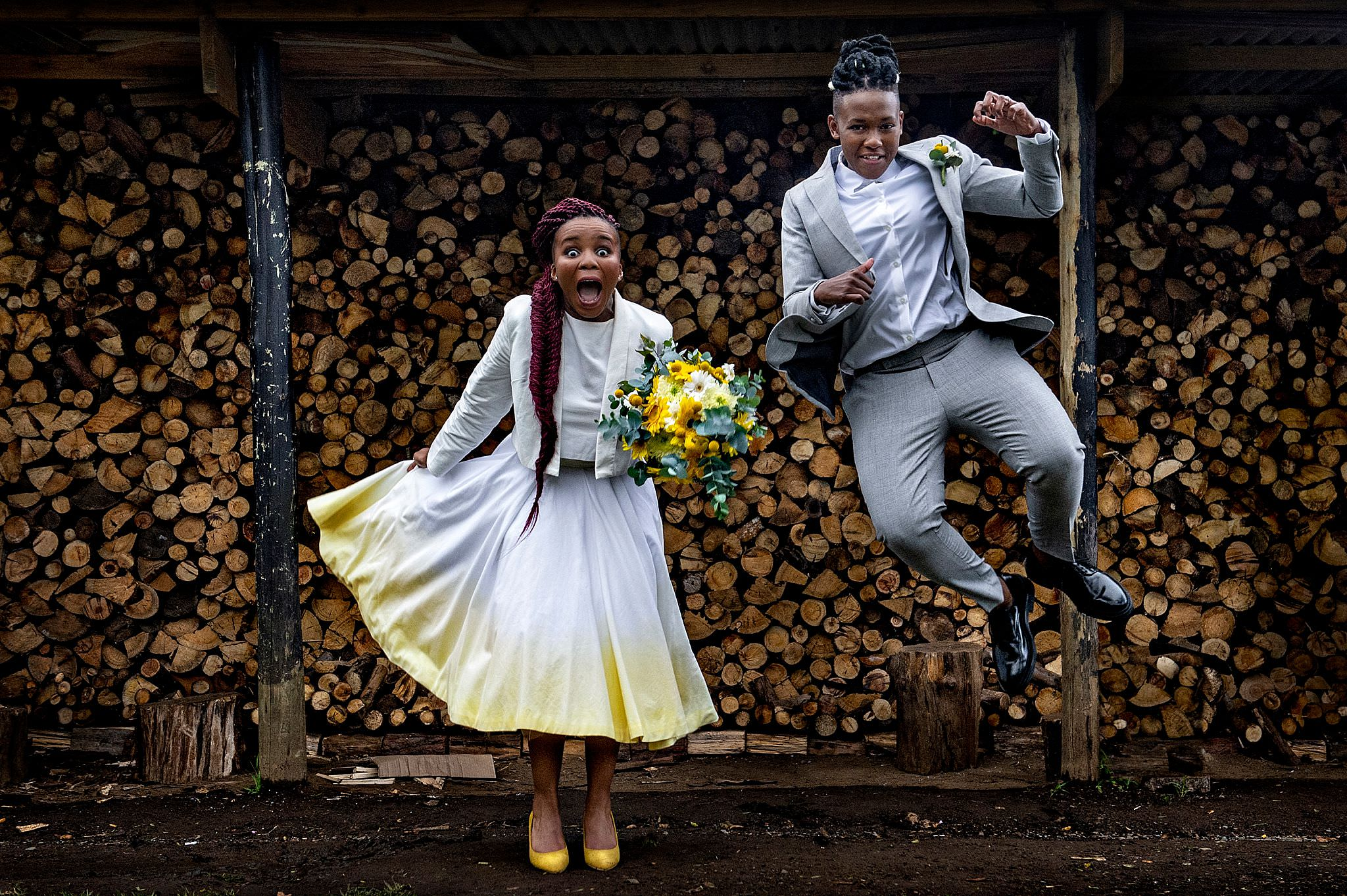 Brides hamming it up against woodpile - photo by Jacki Bruniquel