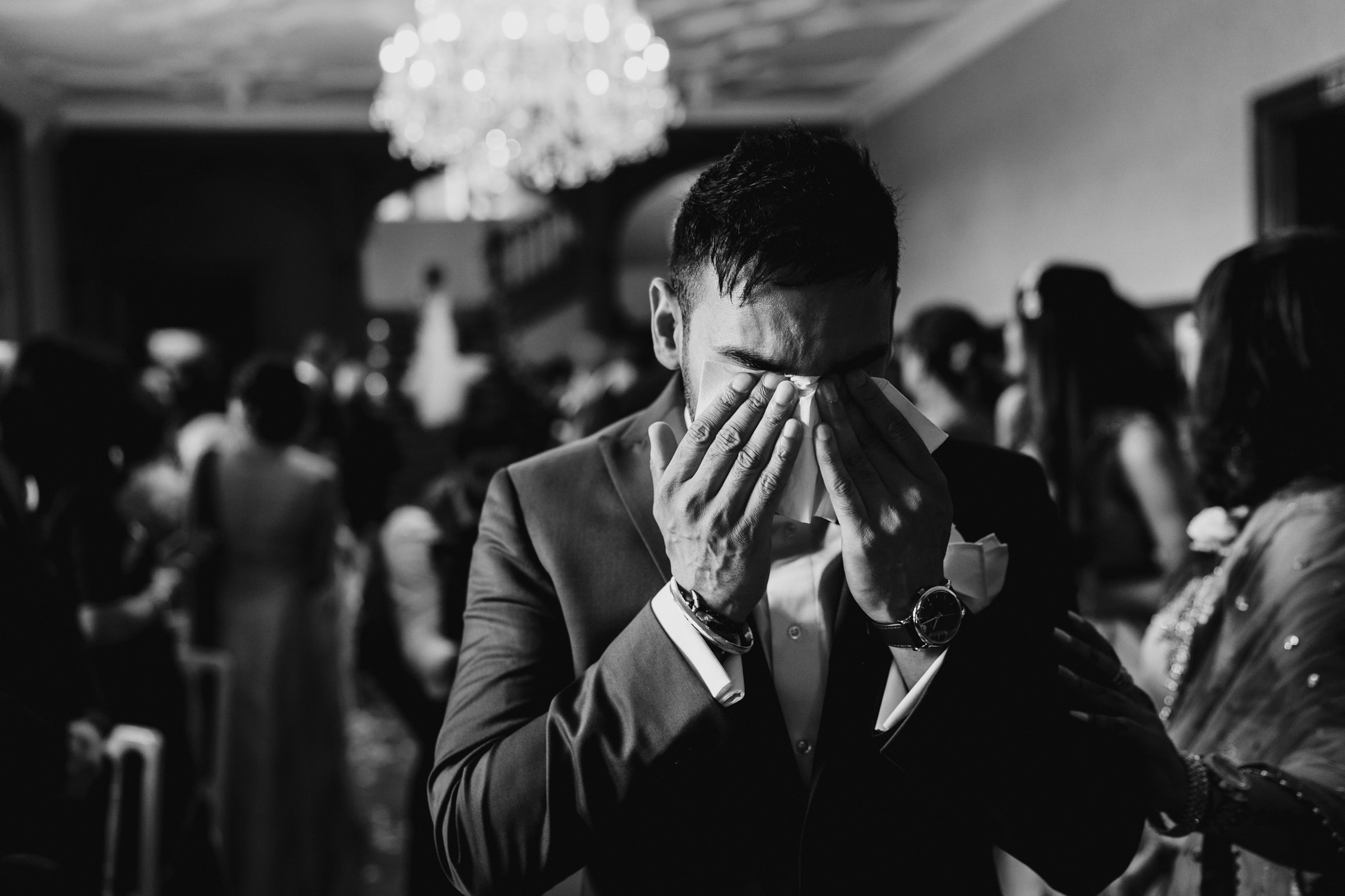 Emotional groom as bride descends staircase - photo by MIKI Studios