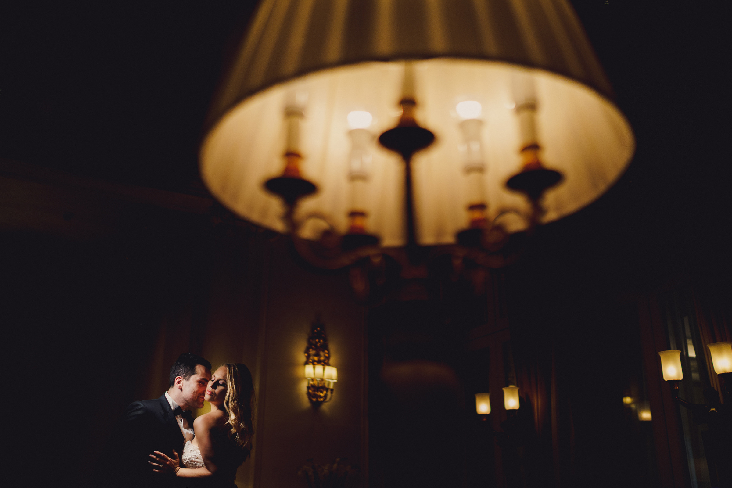 Groom kisses bride by lamplight - photo by MIKI Studios