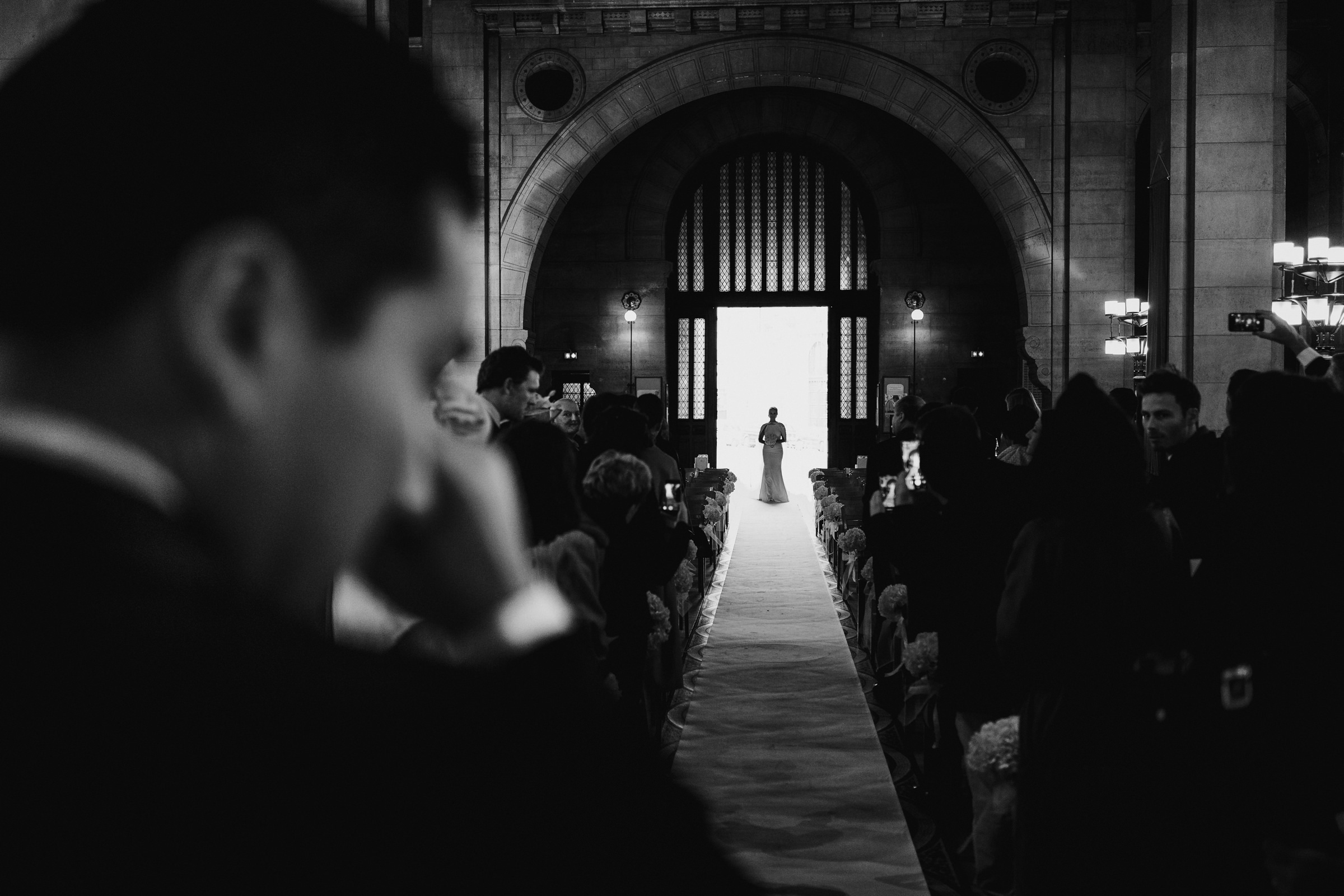 Groom wipes a tear as bride approaches aisle - photo by MIKI Studios