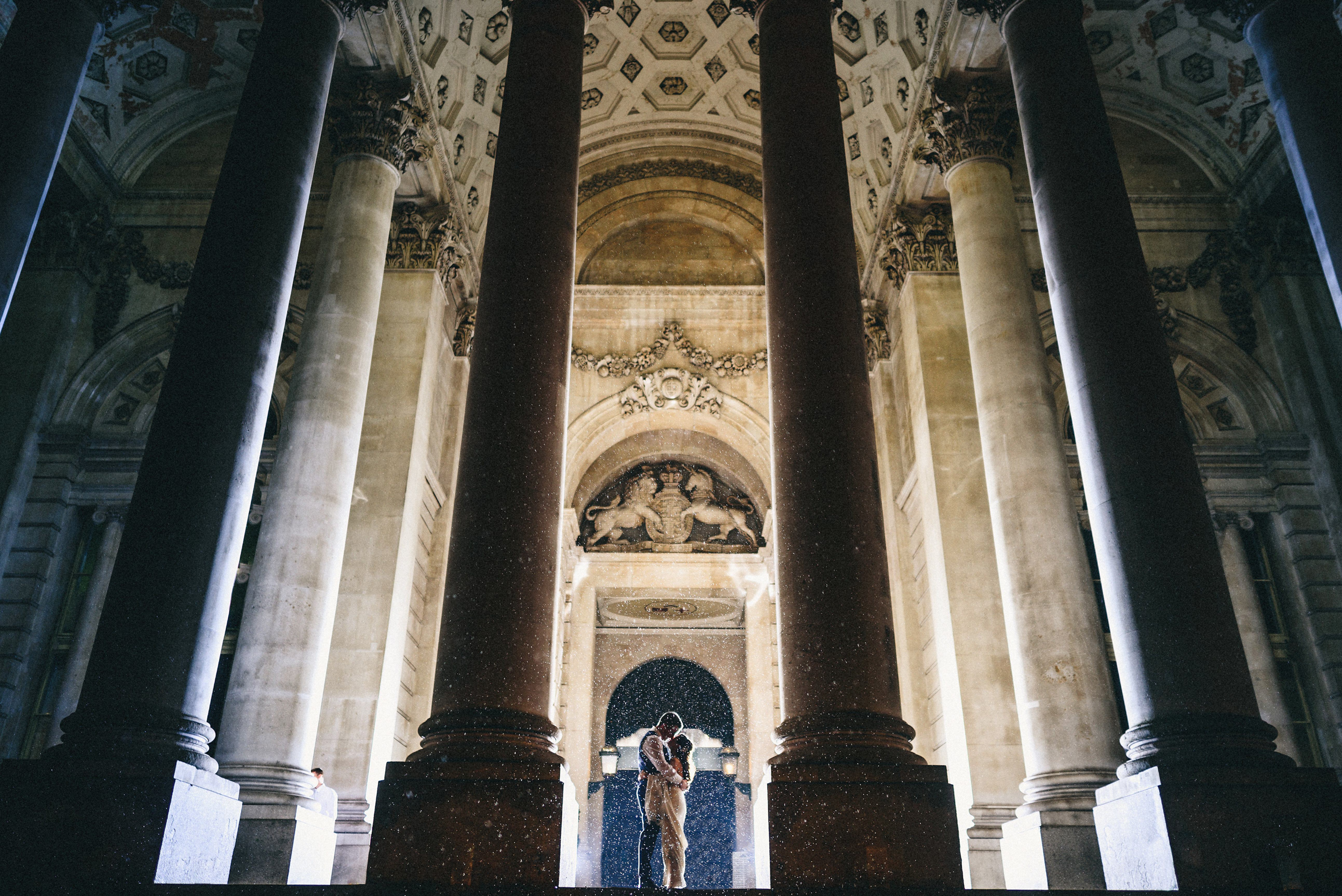 Bride and groom in lit historic building with roman columns - photo by MIKI Studios