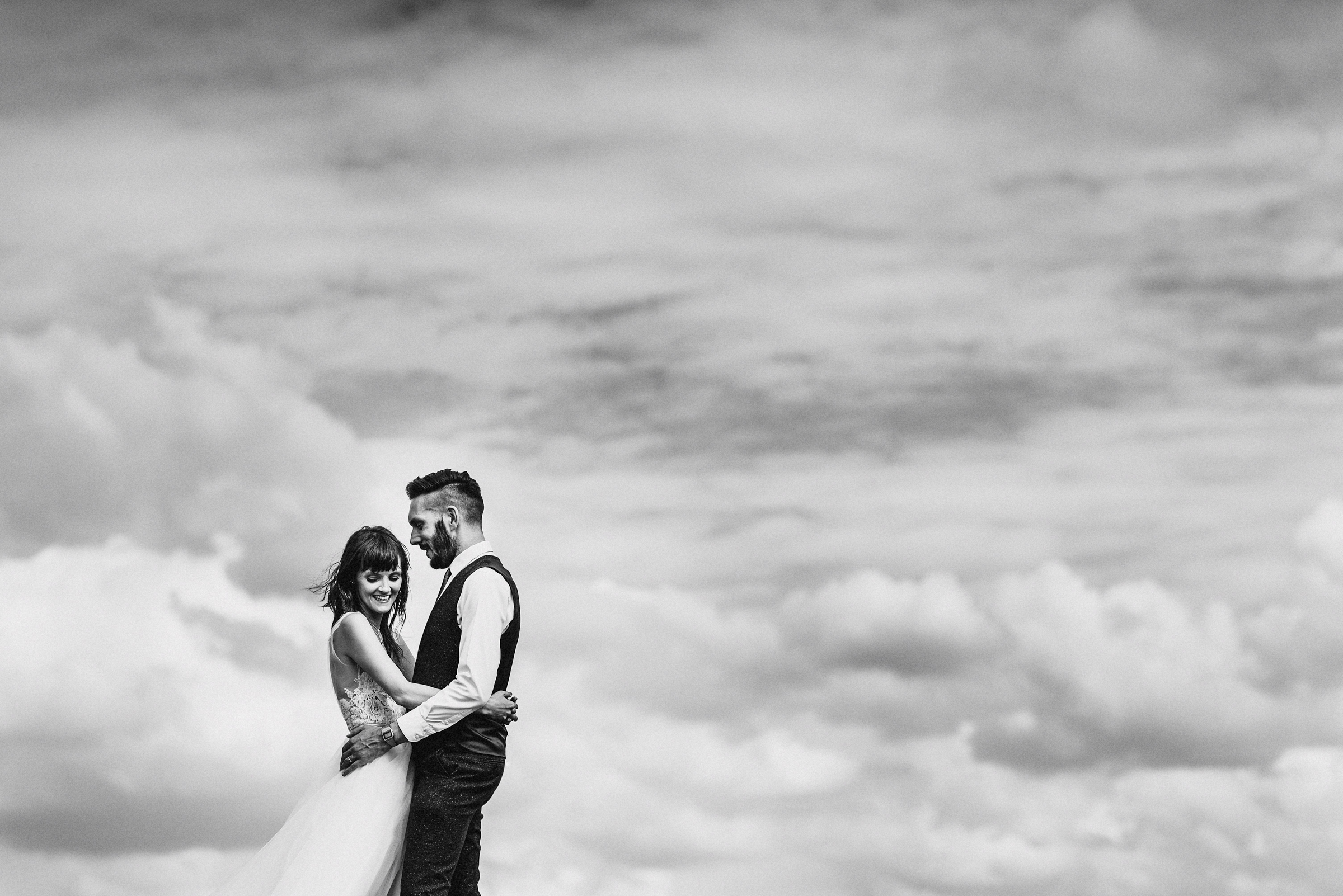 Bride and groom pose against clouds - photo by MIKI Studios