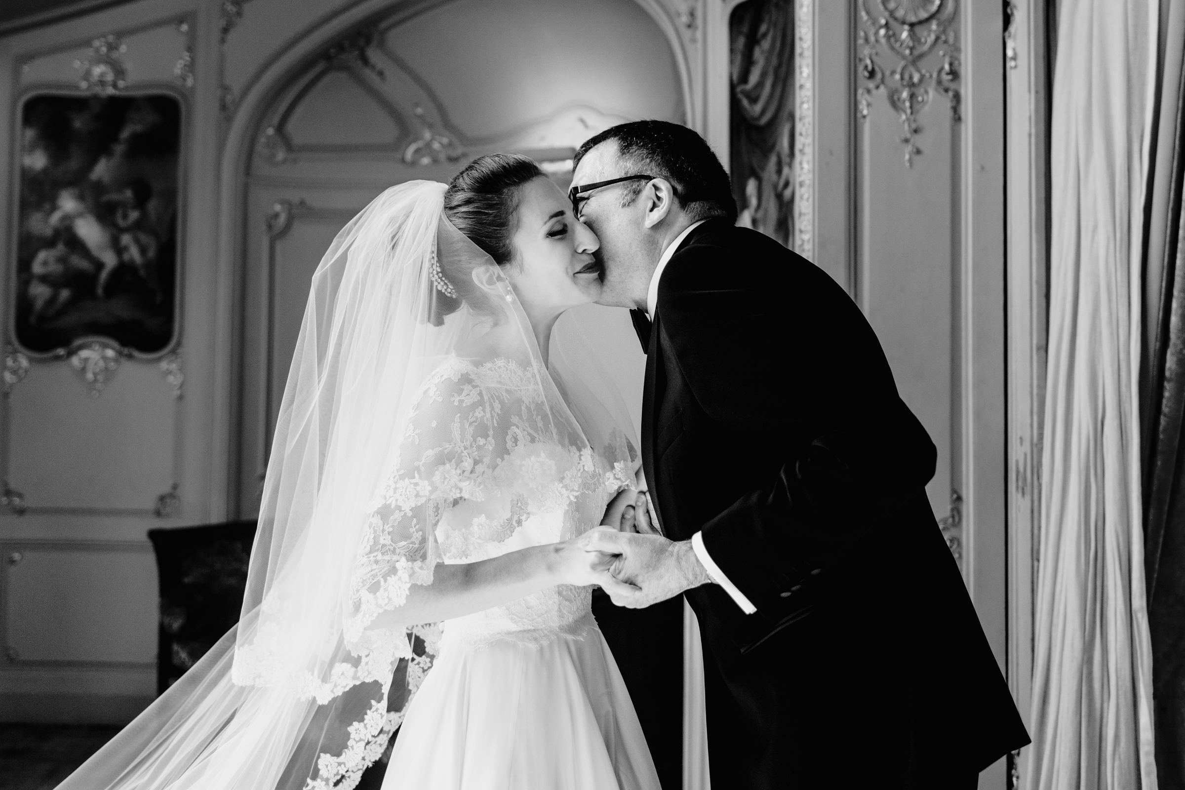 Black and white photo of groom kissing bride in lace gown by MIKI Studios London