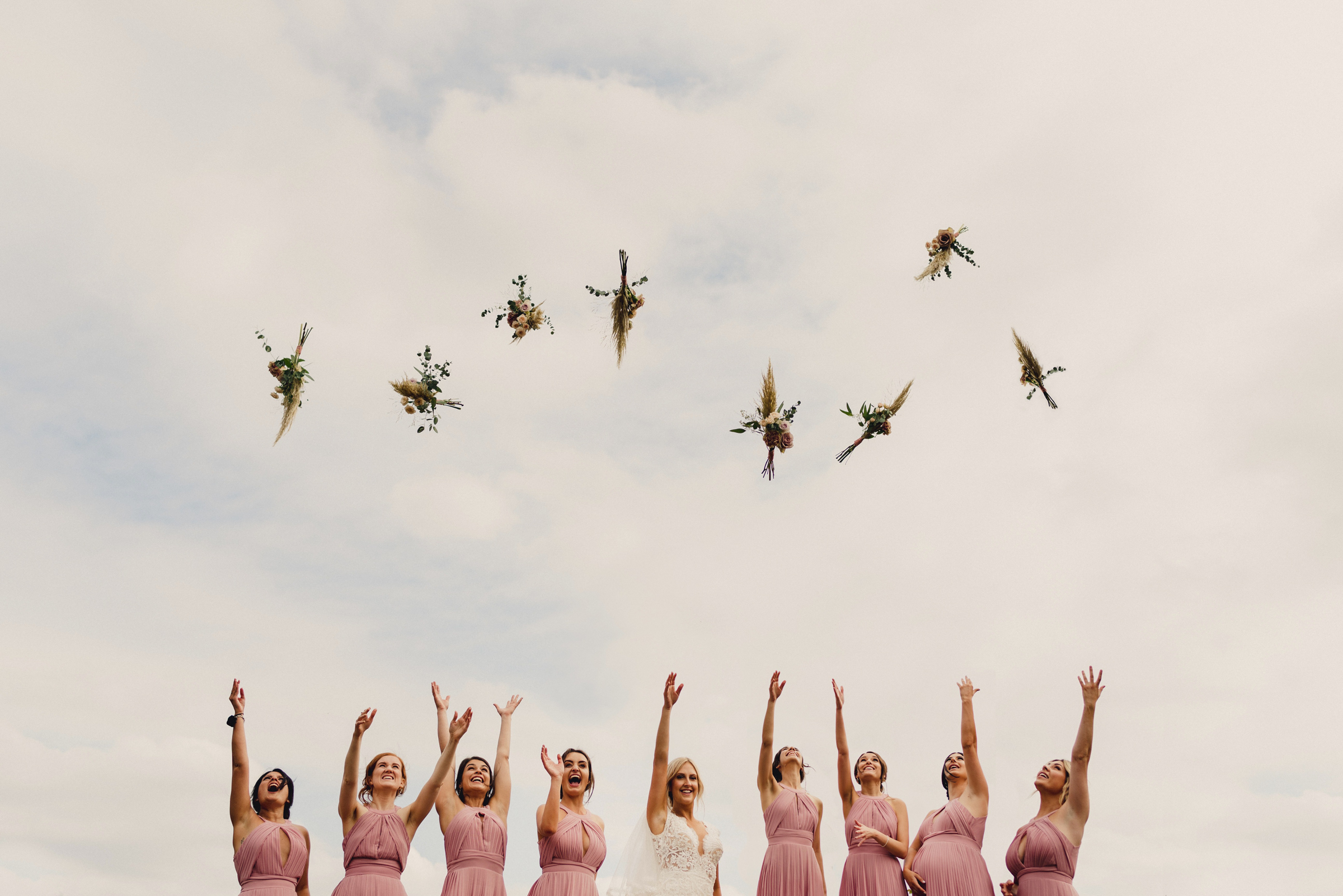 Bridal party in a line tossing bouquets to the sky - photo by MIKI Studios